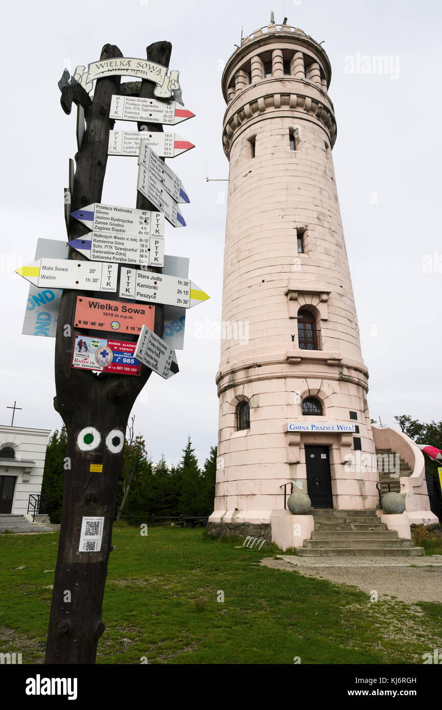Stone viewing tower and hiking trail markers with arrow signs on Wielka Sowa (Great Owl) summit, the highest peak - Stock Image