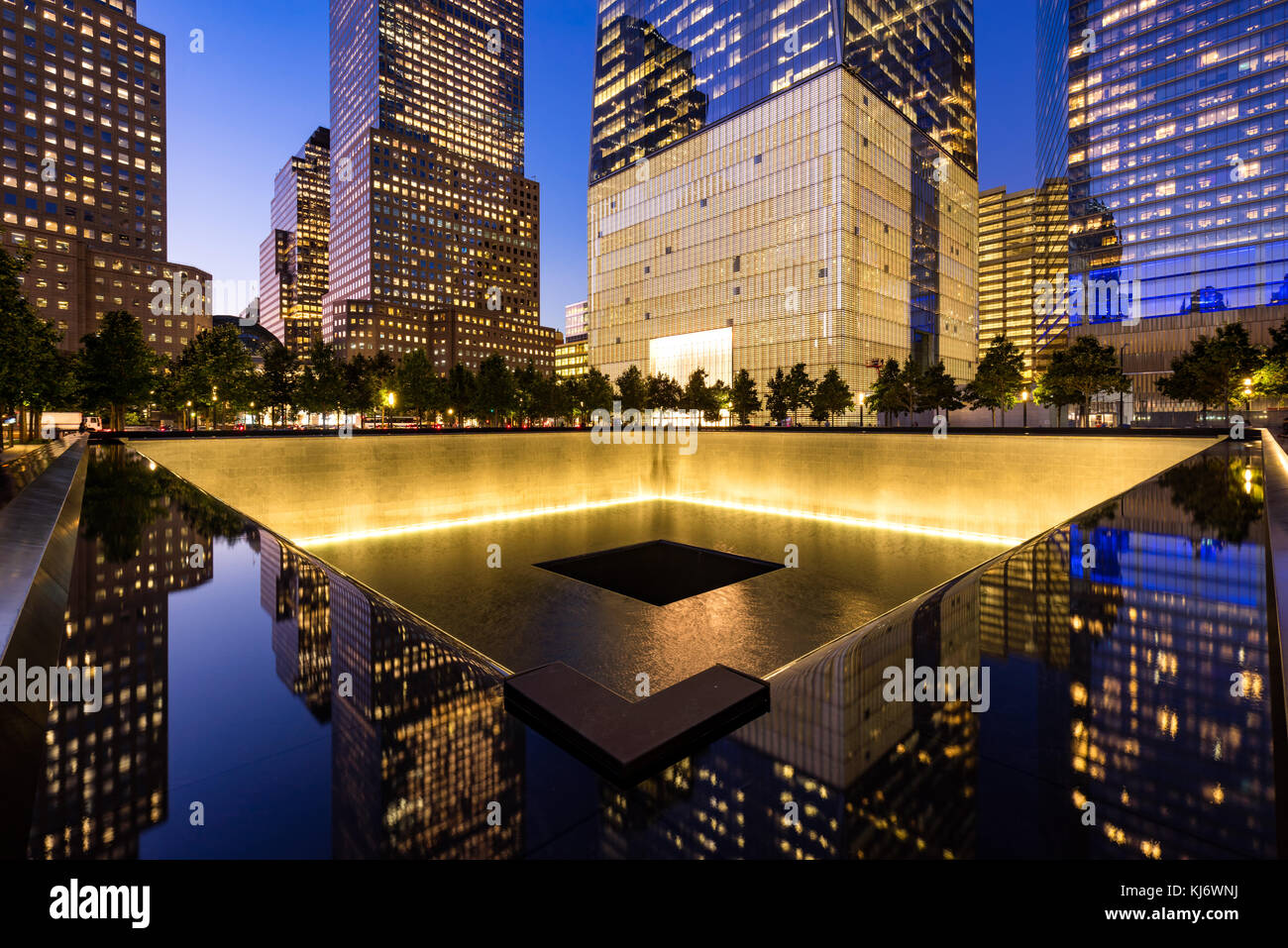 The North Reflecting Pool illuminated at twilight with view of One World Trade Center. Lower Manhattan, 9/11 Memorial - Stock Image