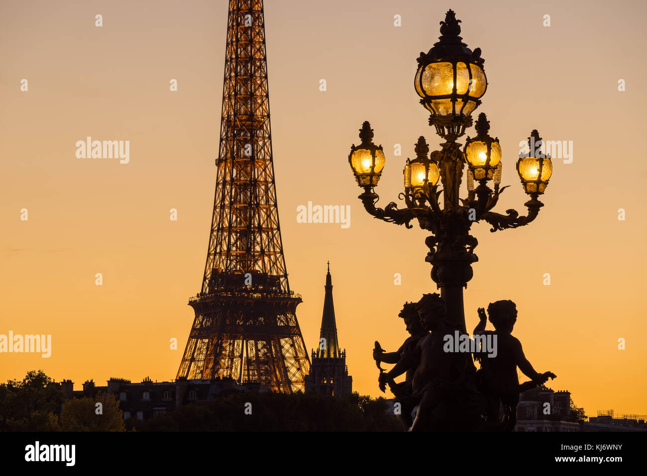 Alexandre III Bridge lamp post silhouette contrasting with the Eiffel Tower at sunset. Paris, France - Stock Image