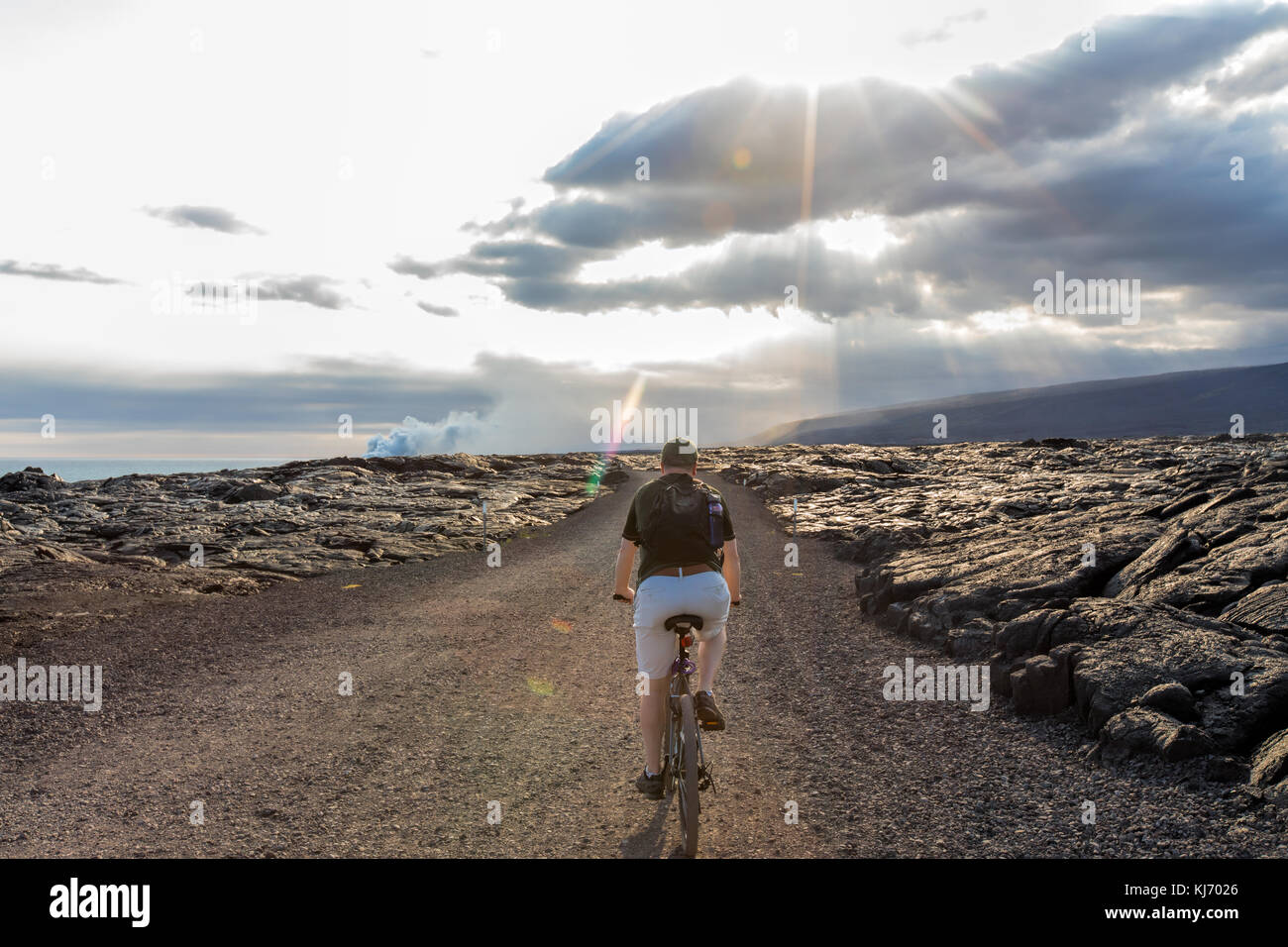 Man riding bicycle through lava field at Volcanoes National Park on the Big Island of Hawaii - Stock Image