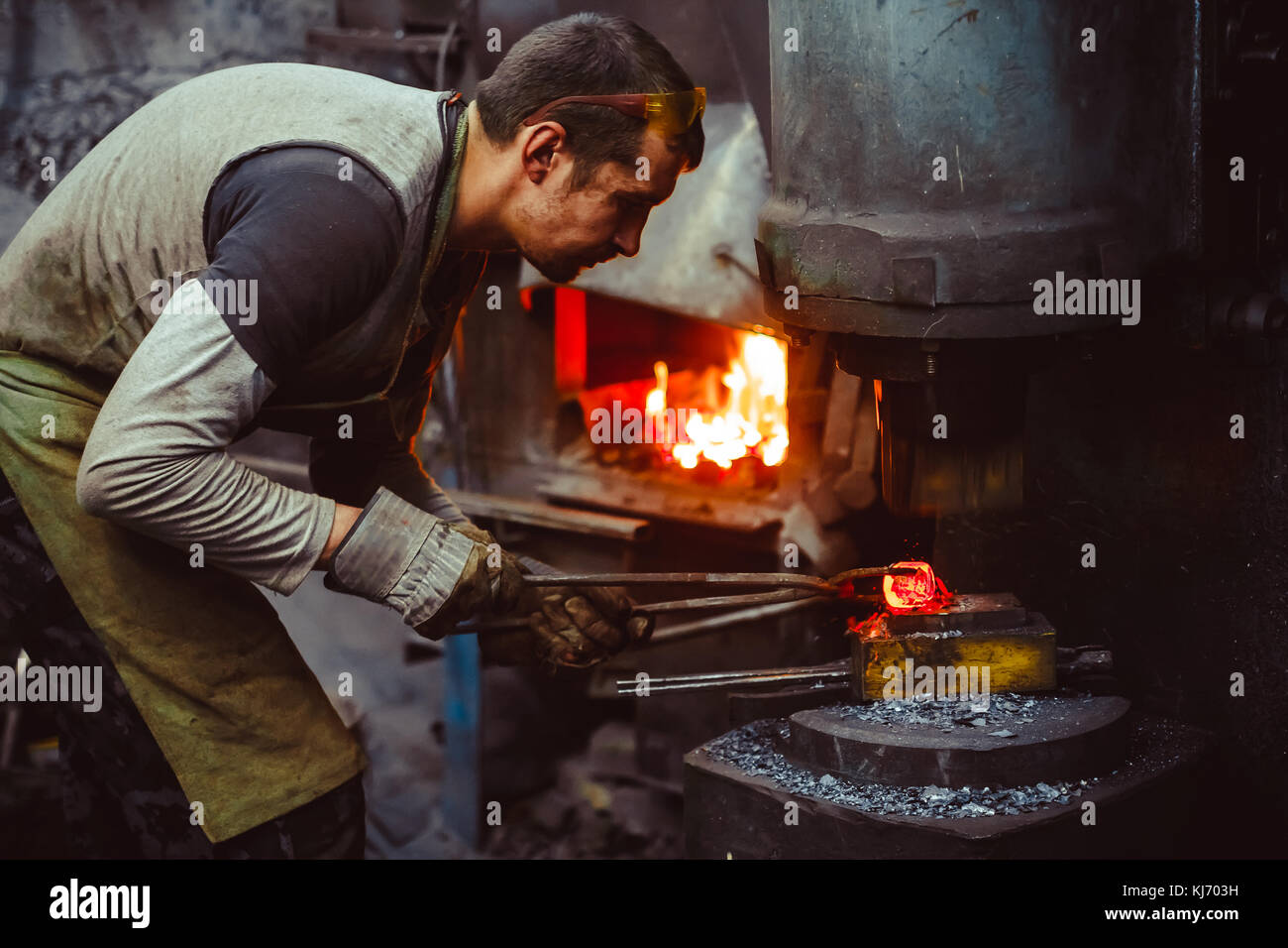 blacksmith working in the forge - Stock Image