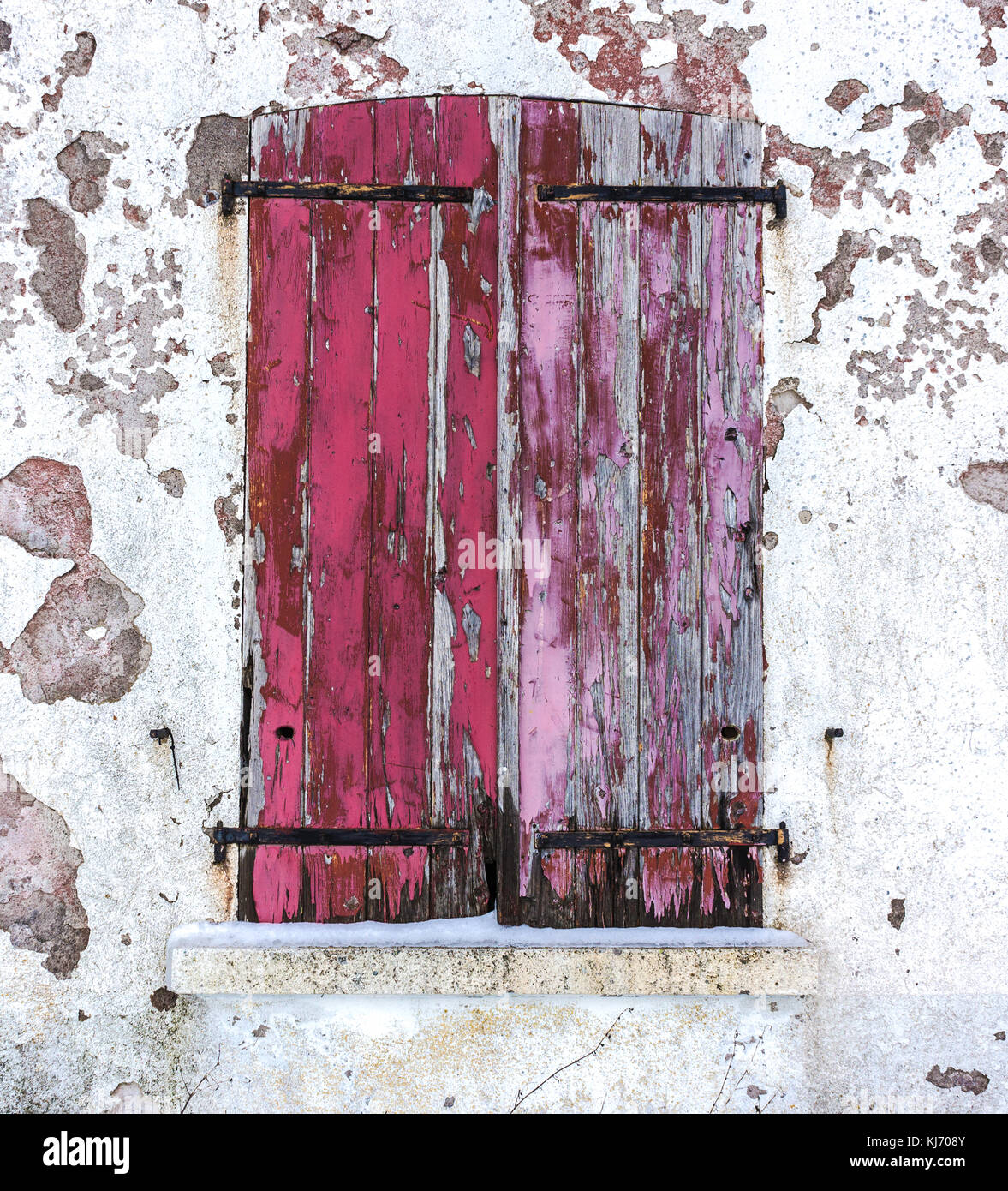 Close-up of an old window with closed red worn wooden shutters on a white decrepit wall in winter. - Stock Image