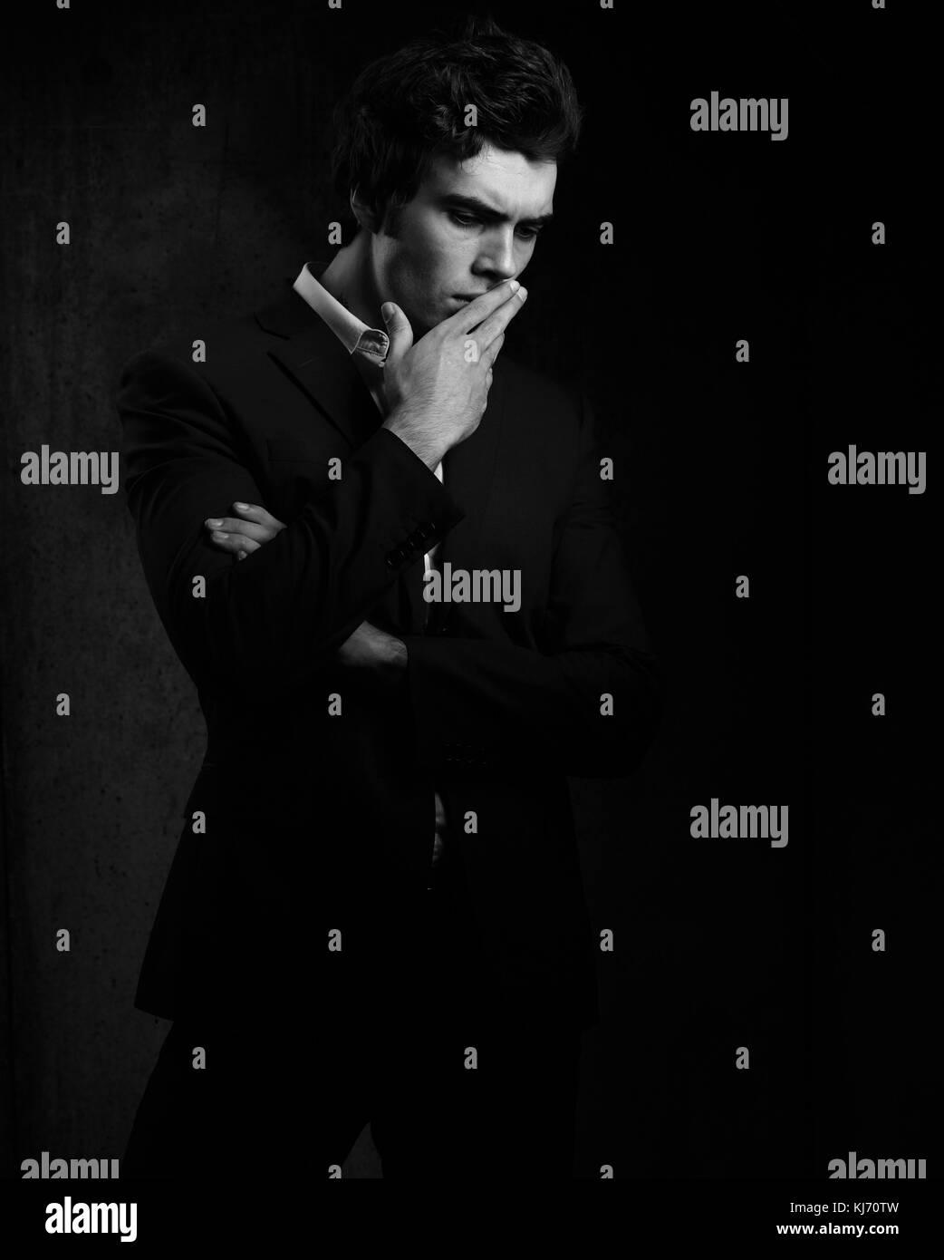 Thinking depression charismatic man looking down on dark shadow dramatic light background. Closeup portrait. Black - Stock Image