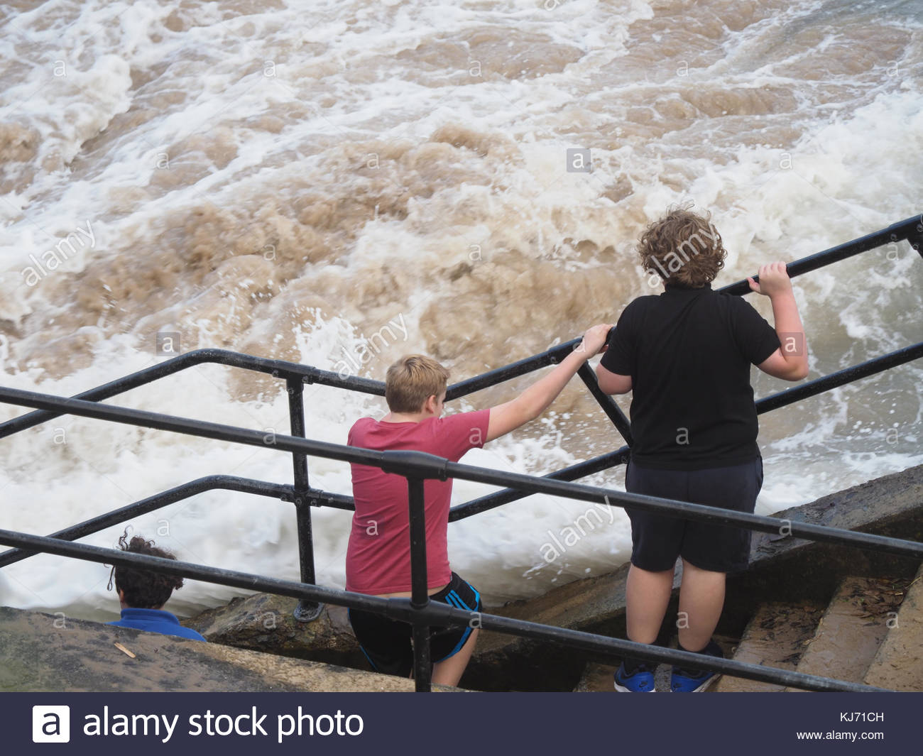 Teenage Children playing chicken and dodging the waves at Tenby Pembrokeshire - Stock Image