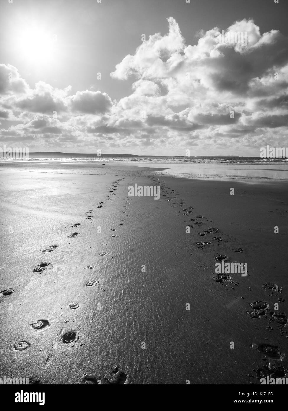 Footsteps across the sand towards the sea at Druidstone Beach Pembrokeshire National Park Wales at Low tide - Stock Image