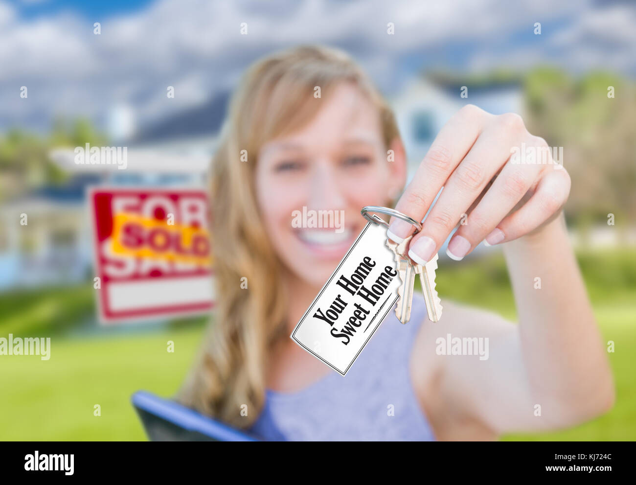 Woman Holding New House Keys with Your Home Sweet Home Card In Front of Sold Real Estate Sign and Home. - Stock Image
