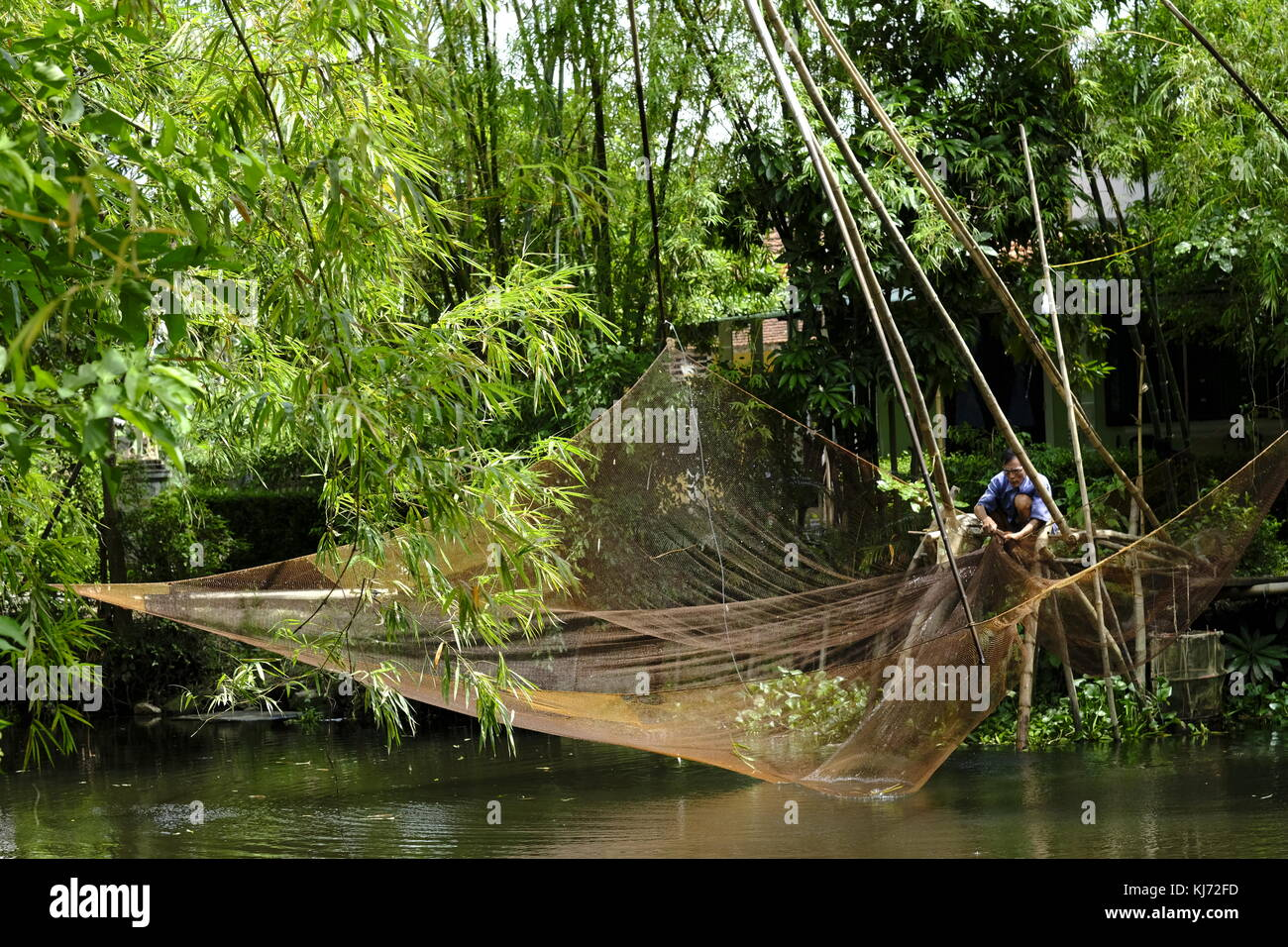 Asian man mending a lift fishing net next to a river in Vietnam - Stock Image