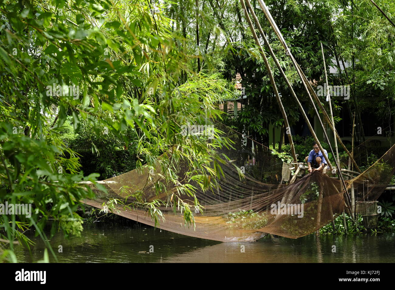 Asian man mending a lift fishing net next to a river in Vietnam - Stock Image