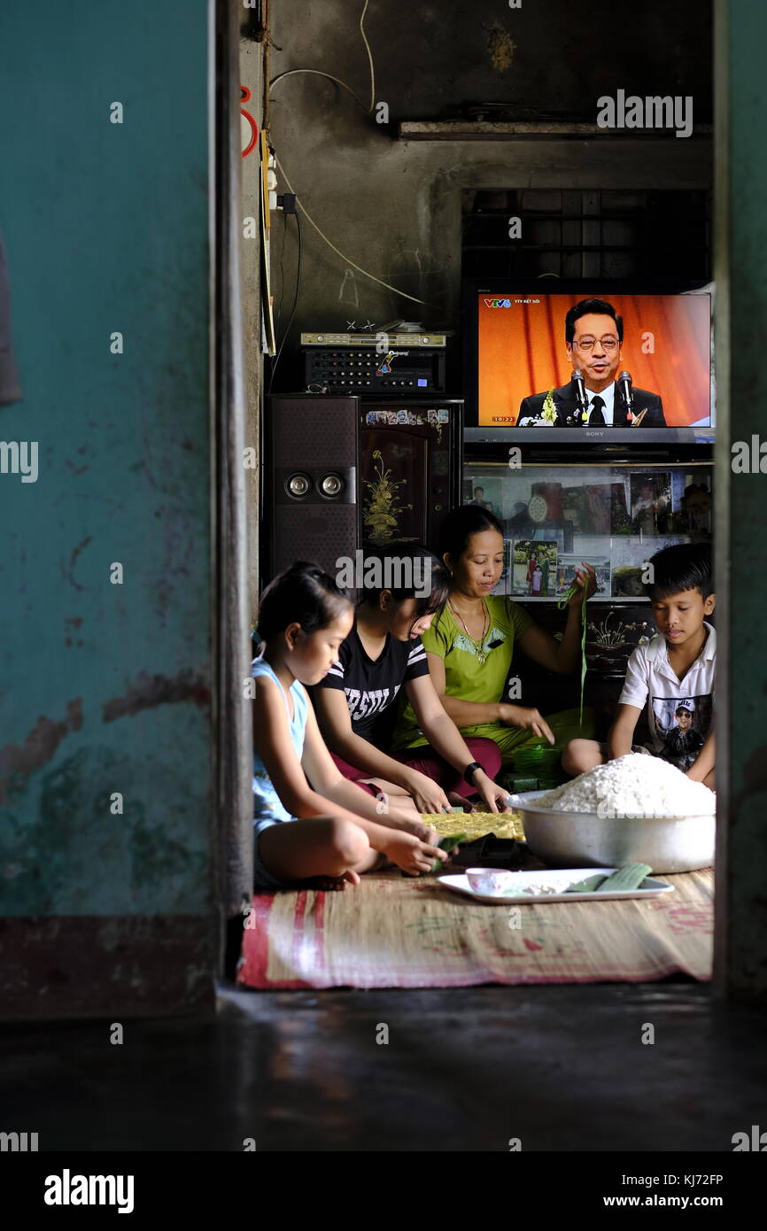Vietnamese family preparing rice pancakes for market at home in a local village - Stock Image