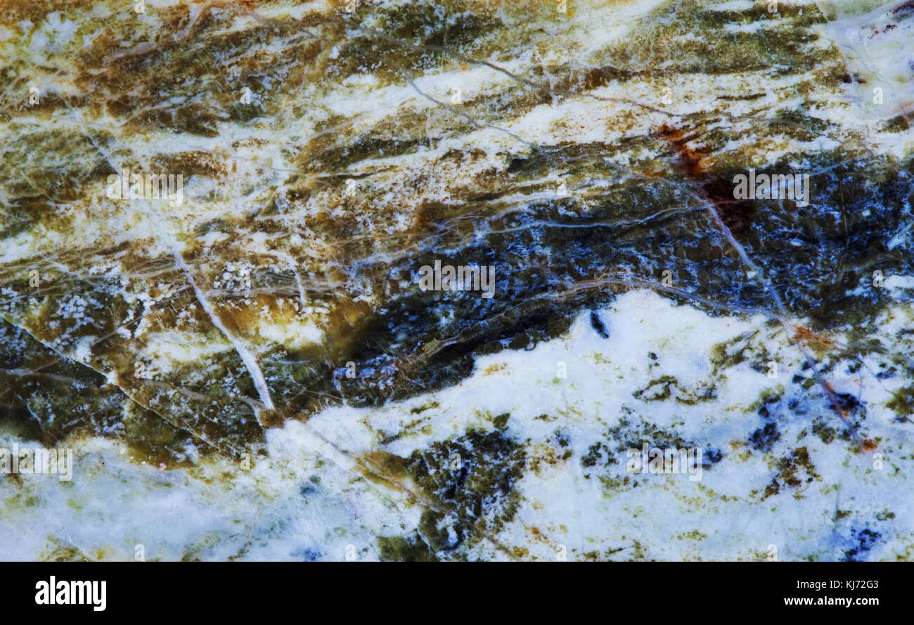 Serpentine subgroup mineral stone macro view. Greenish brownish color polymorphs asbestos gem background - Stock Image