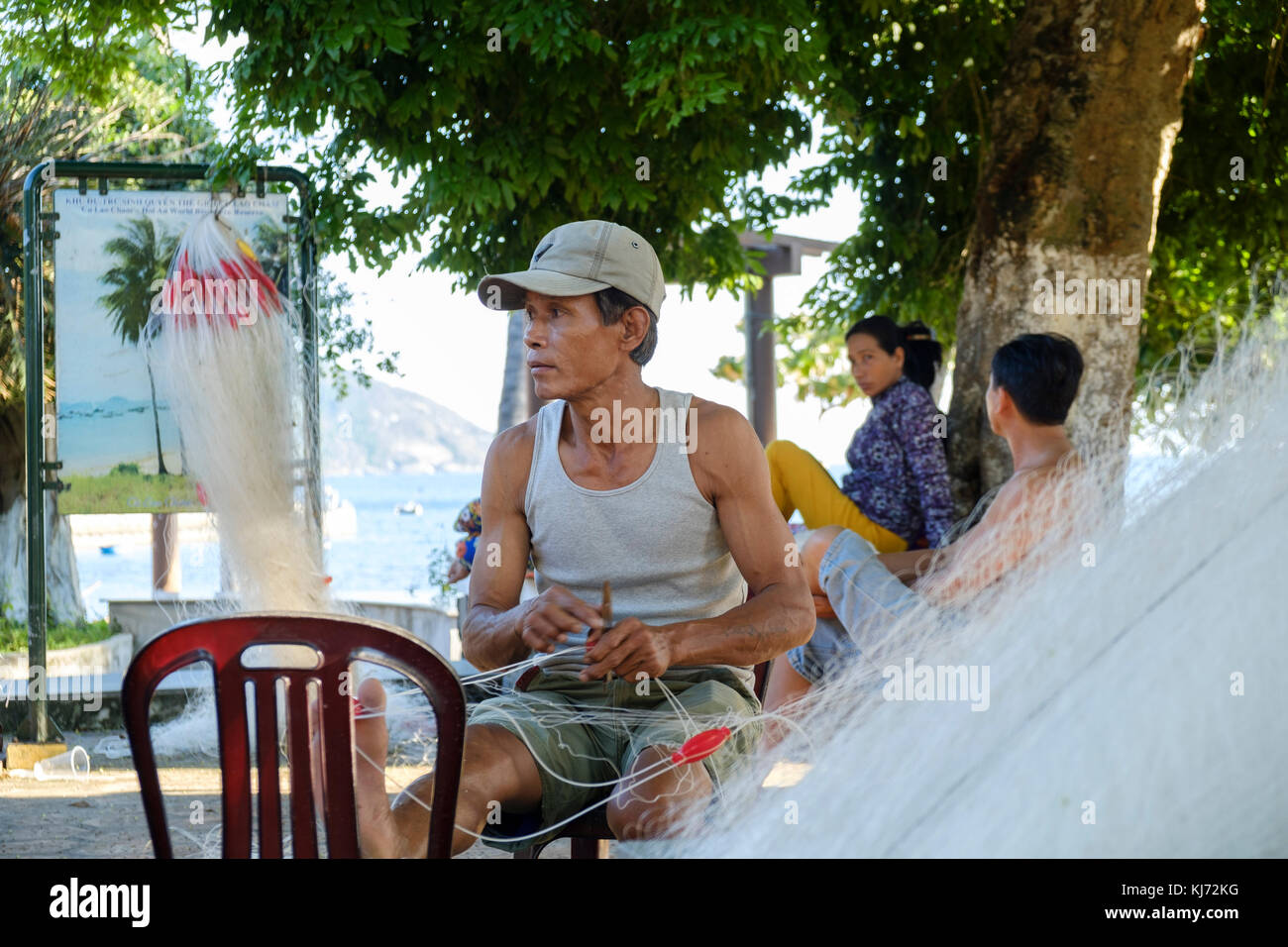 Vietnamese fisherman repairing his fishing net in a coastal village - Stock Image