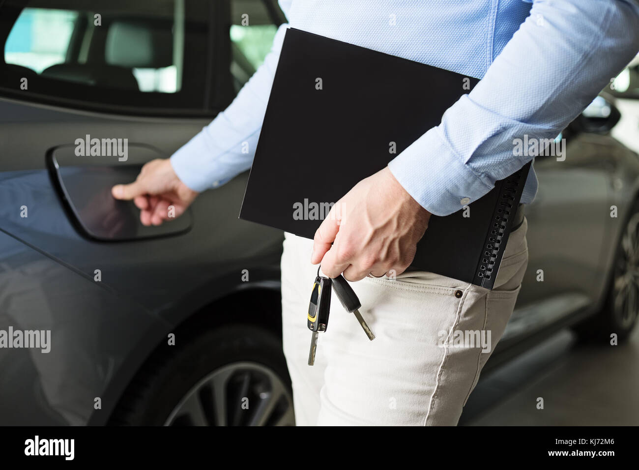 Close up of male adult car dealer standing indoors at car dealership,holding a folder and car keys in his hand, - Stock Image