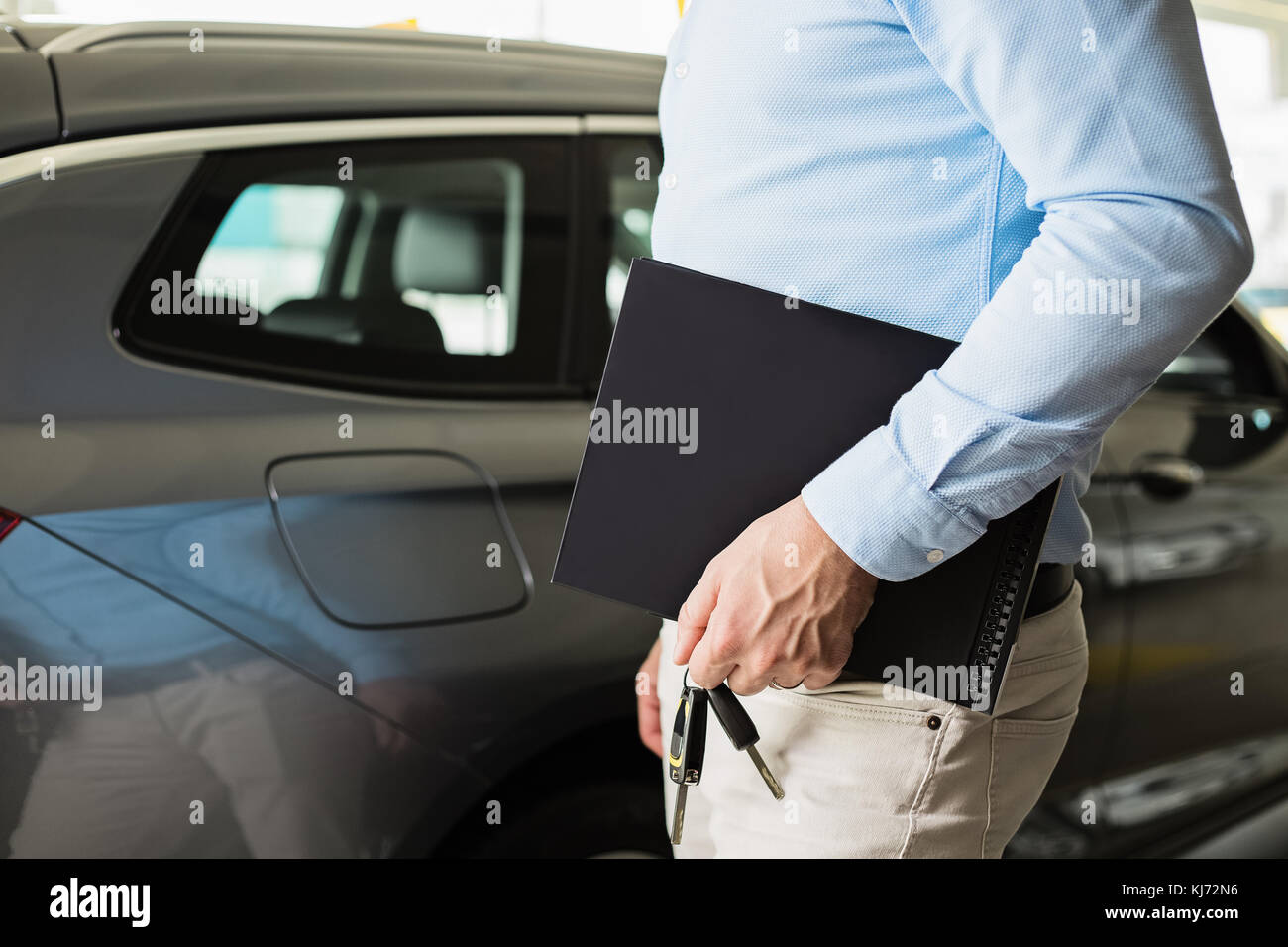 Close up of male adult car dealer standing indoors at car dealership, holding a folder and car keys in his hand - Stock Image