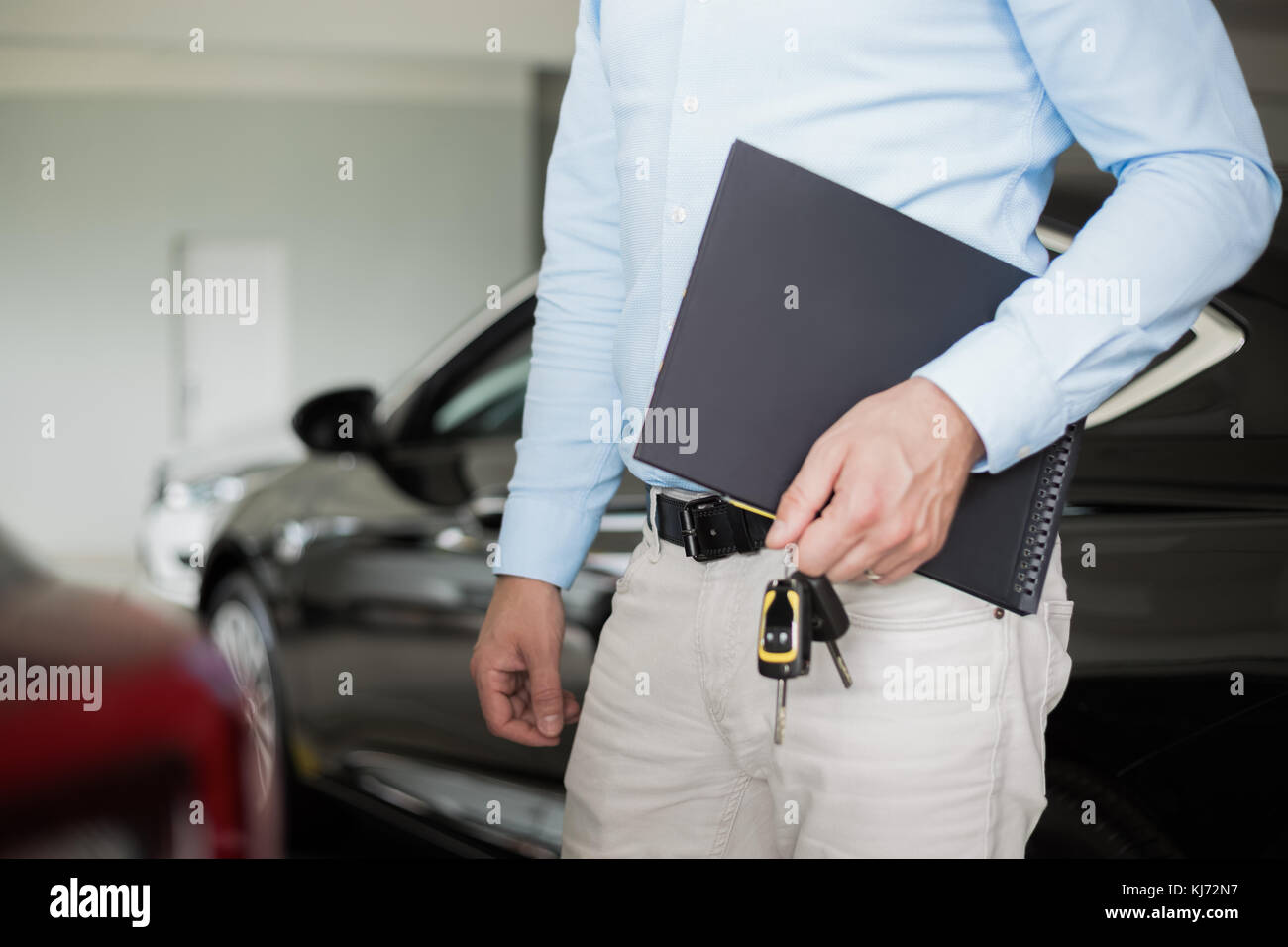 Close up of male adult car dealer standing indoorts at car dealership,holding a folder and car keys in his hand - Stock Image