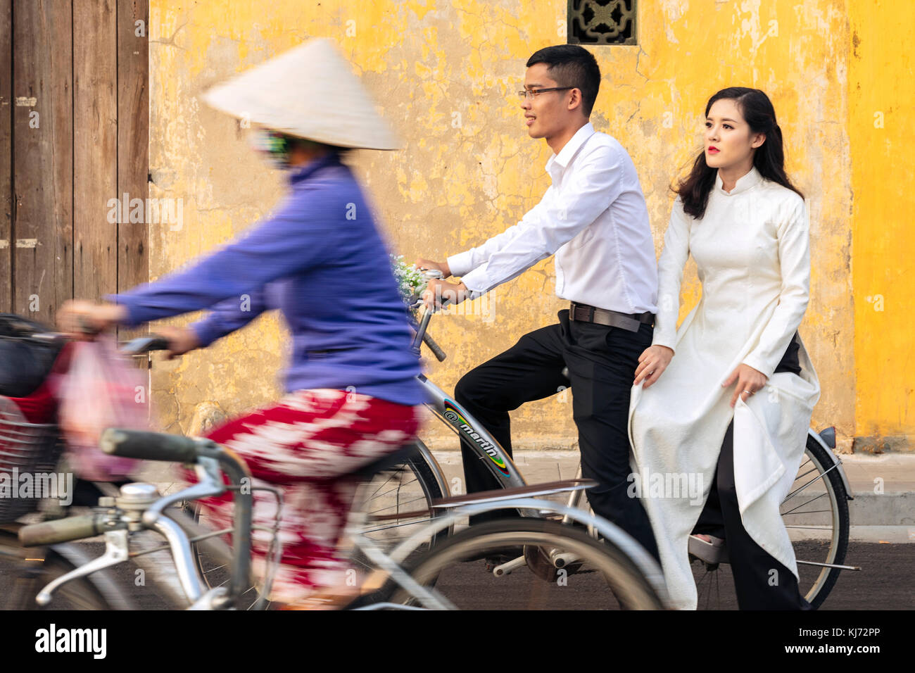 Young Newly Married Couple on a Bicycle in the Unesco World Heritage listed history centre of Hoi An, Vietnam - Stock Image