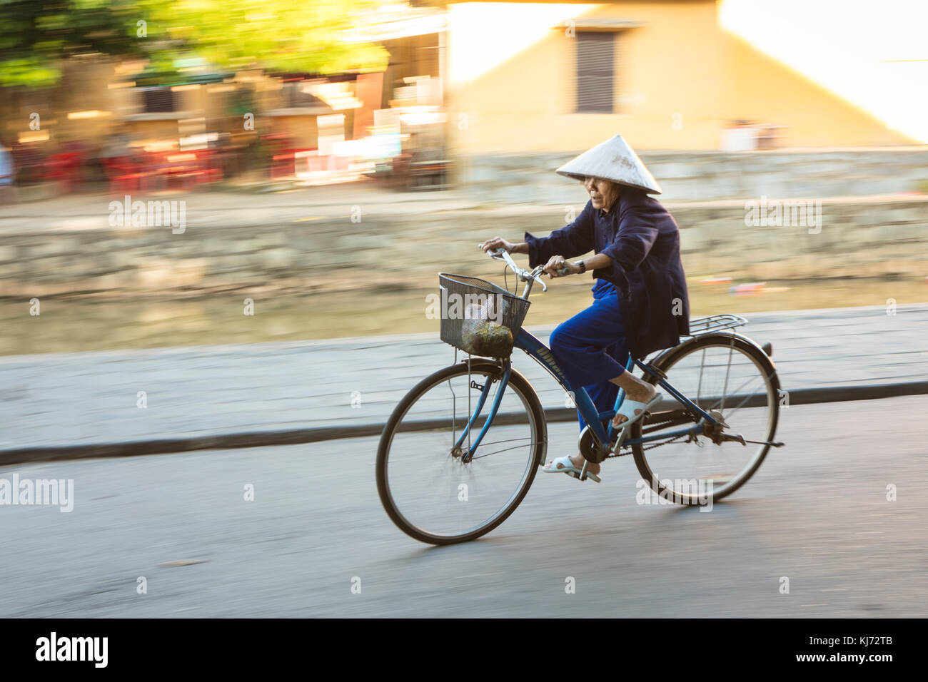Elderly Asian commuter in a conical hat cycling in Hoi An city streets - Stock Image