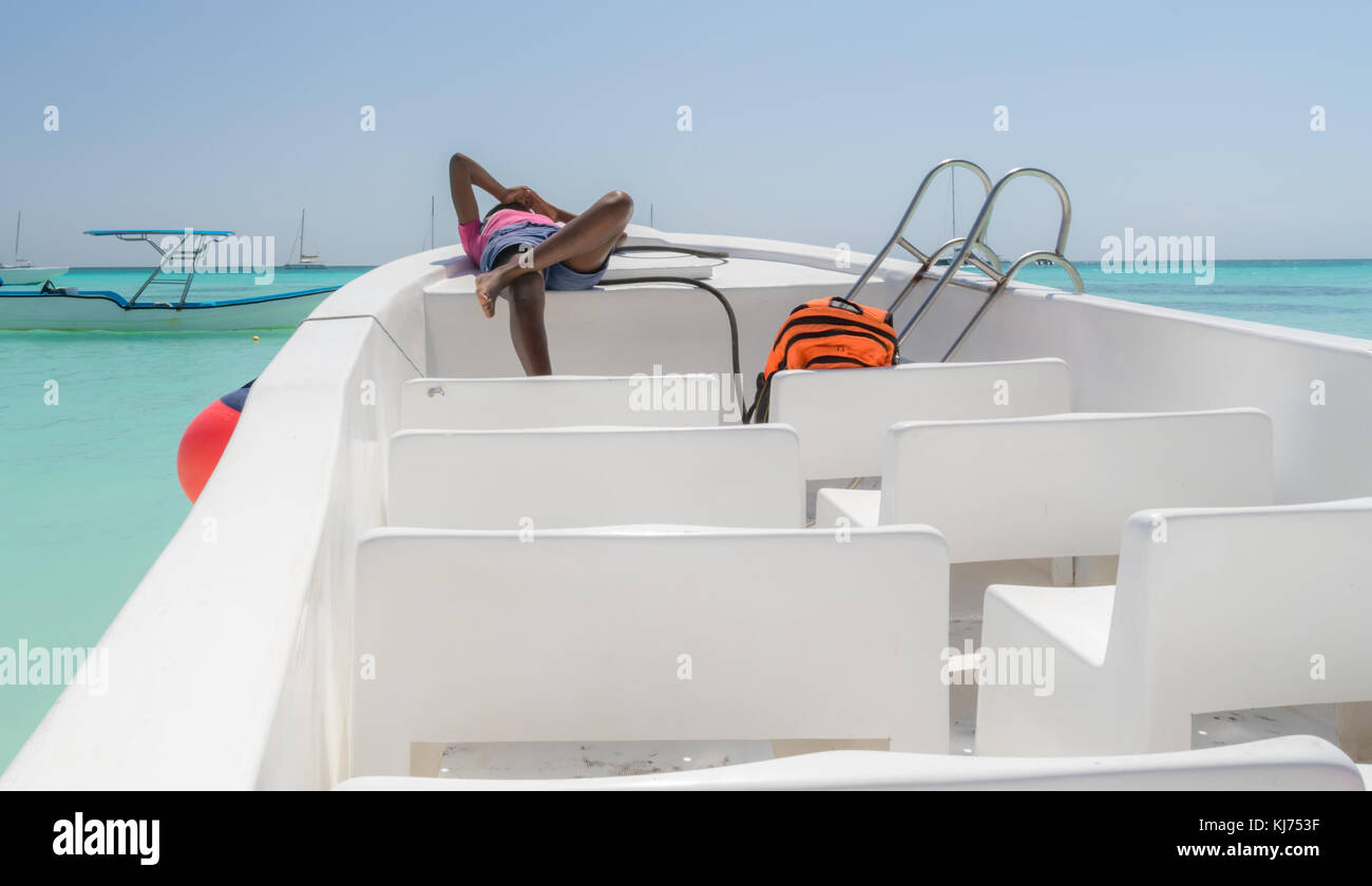 The dark-skinned girl resting on a boat moored at the shore of the island of Saona, Dominican Republic. - Stock Image