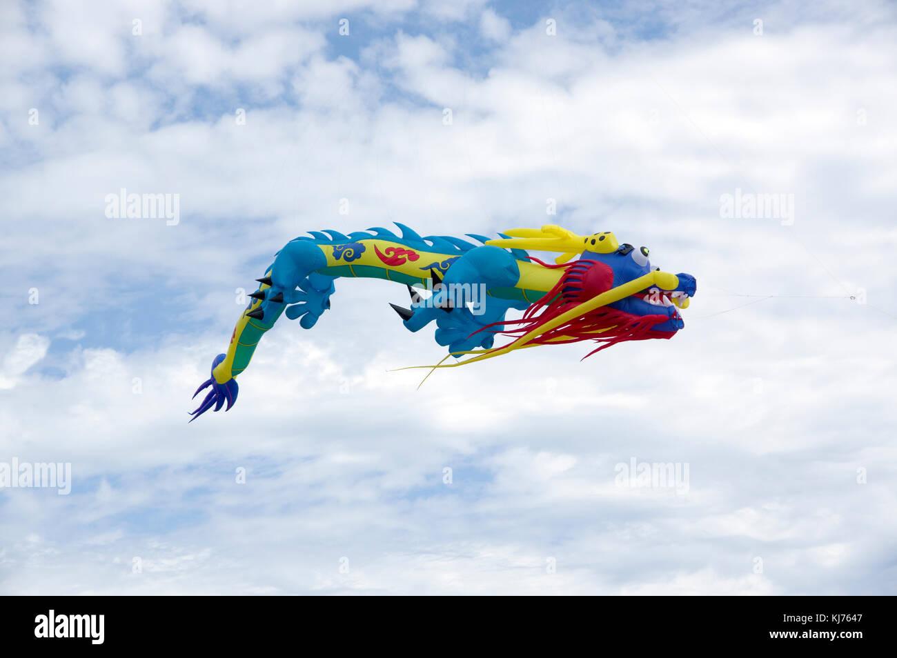 Dragon kite flying over Neshotah Beach, Two Rivers, Wisconsin during Kites Over Lake Michigan annual kite festival. - Stock Image