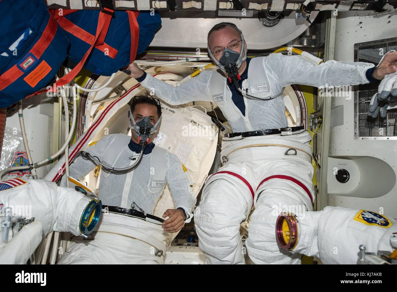 Expedition 53 American astronaut Randy Bresnik, right, and Joe Acaba practicing putting on their spacesuits aboard Stock Photo