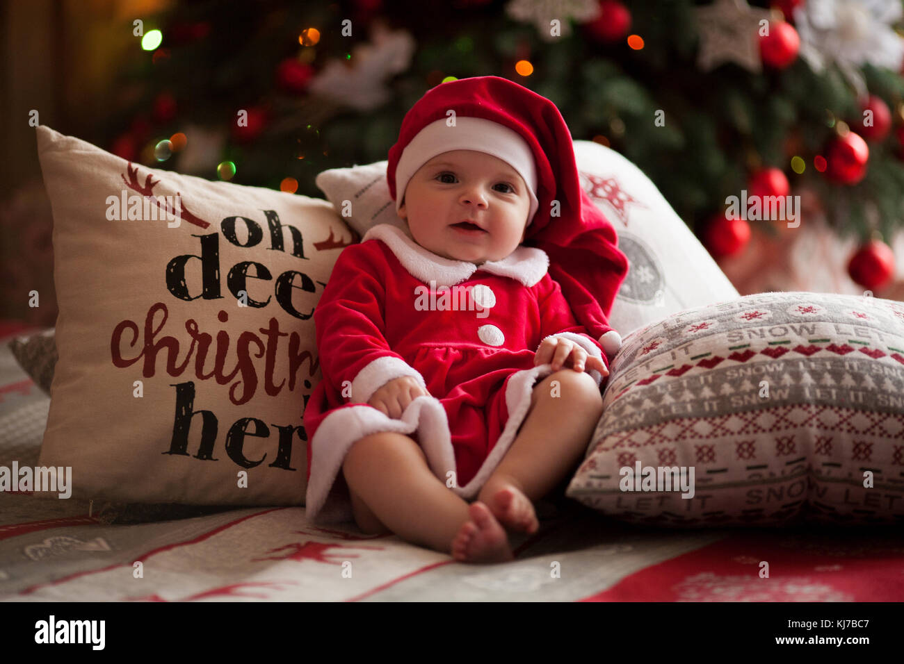 a6bbe0863 Baby girl in Santa Claus costume and hat smiles and sits barefoot on bed  among pillows