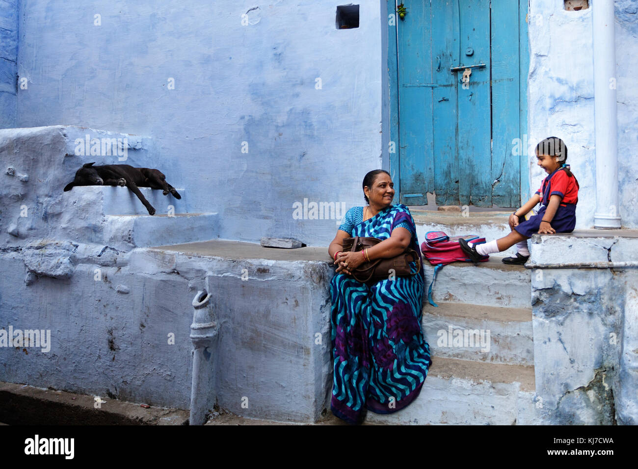Happy little indian girl sitting on the stairs with her grandma in front of a blue house in Jodhpur, Rajasthan, Stock Photo