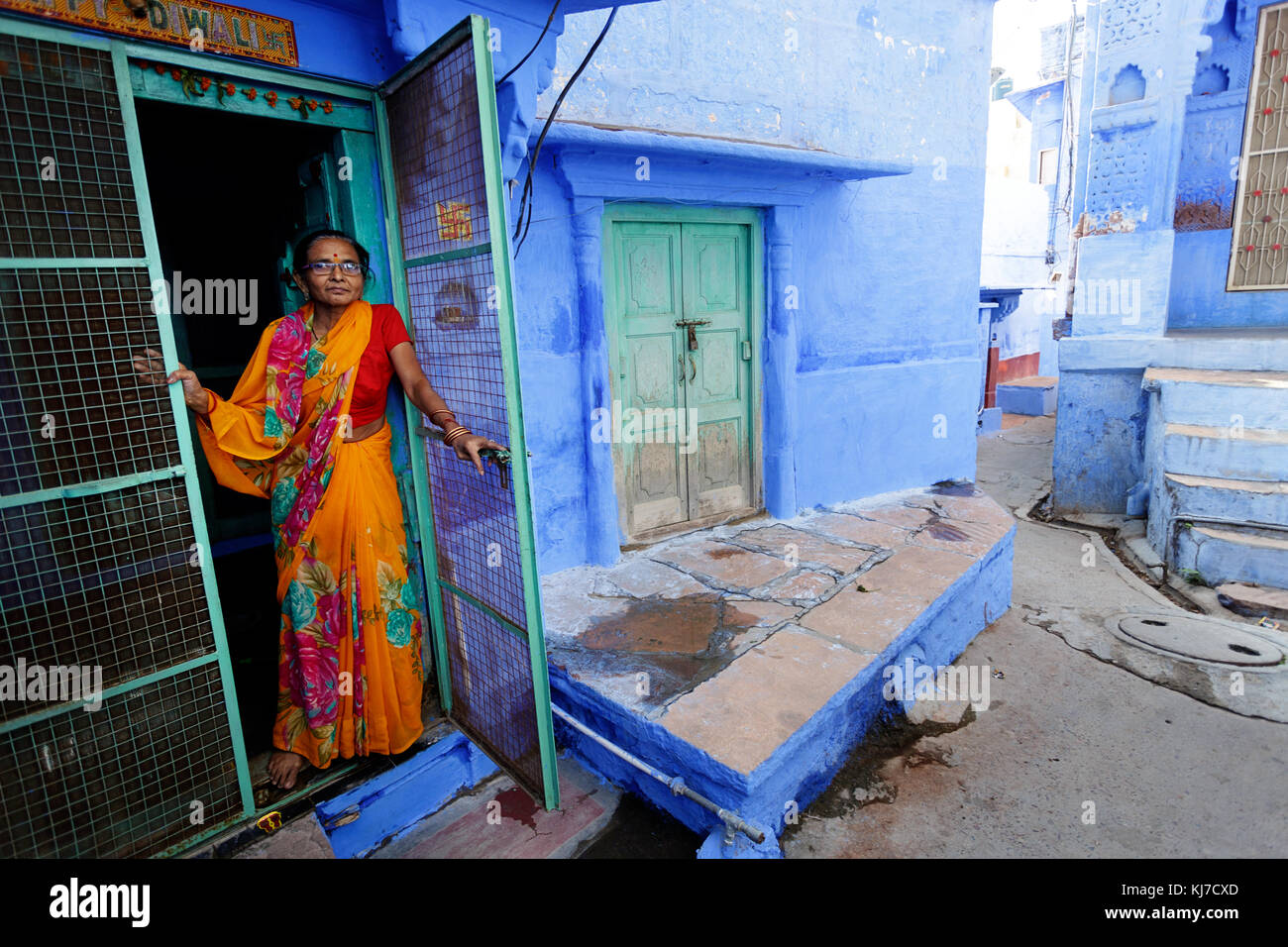Old indian woman dressed in traditional clothes opening the green entrance door, Jodhpur, India. Stock Photo