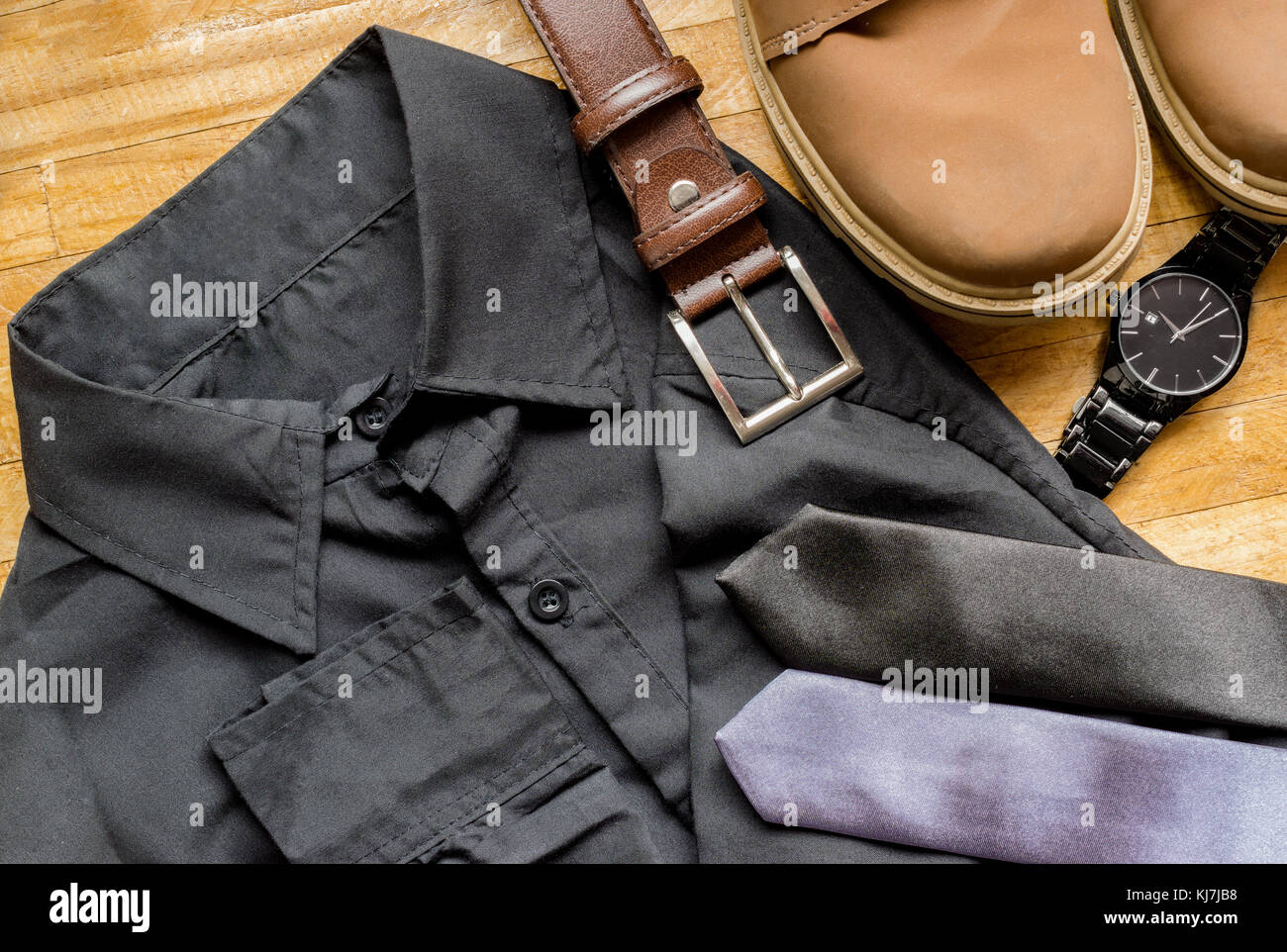 Men's clothes on top of a wooden surface, showing a black dress shirt, brown leather belt, brown boots, neckties - Stock Image