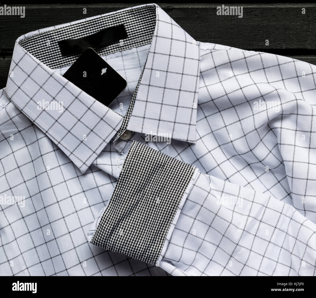 Men's white stripped checkered dress shirt, brand new, with tags, on top of black wooden surface Stock Photo
