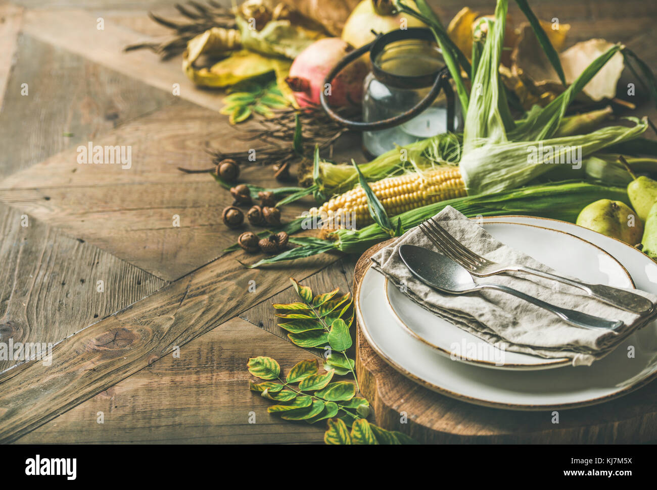 Fall table setting for Thanksgiving day celebration. Plate, cutlery, candle holder, Autumn seasonal vegetables, - Stock Image