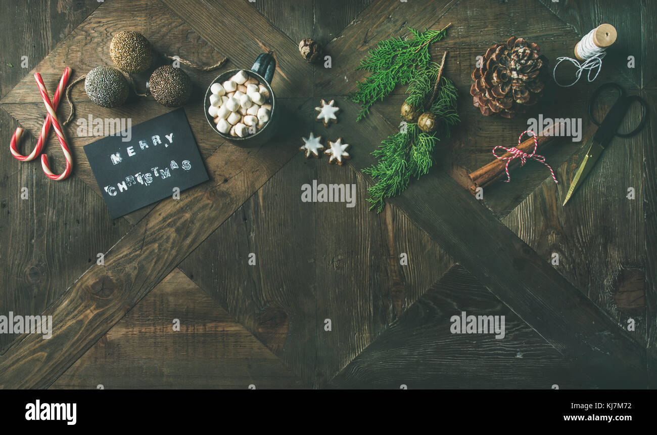 Christmas or New Year holiday celebrating background. Flat-lay of greeting card, glittering toys, hot chocolate, - Stock Image