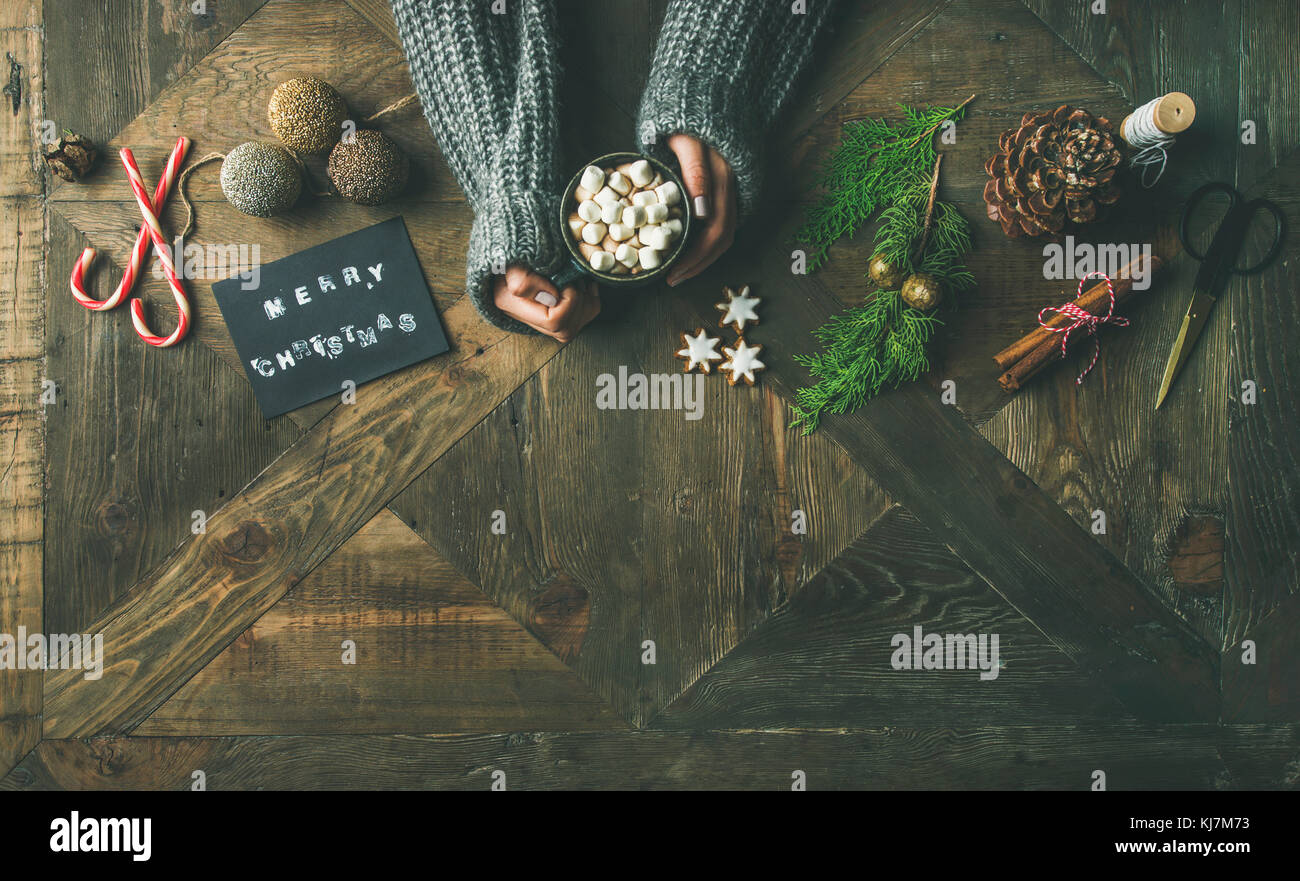 Christmas, New Year holiday preparation background. Flat-lay of greeting card, glittering toys, woman's hands - Stock Image
