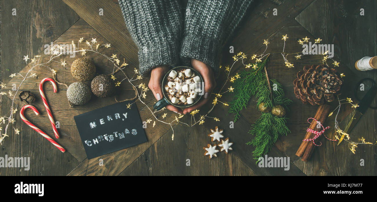 Christmas, New Year holiday background. Flat-lay of greeting card, glittering toys, woman's hands holding mug - Stock Image