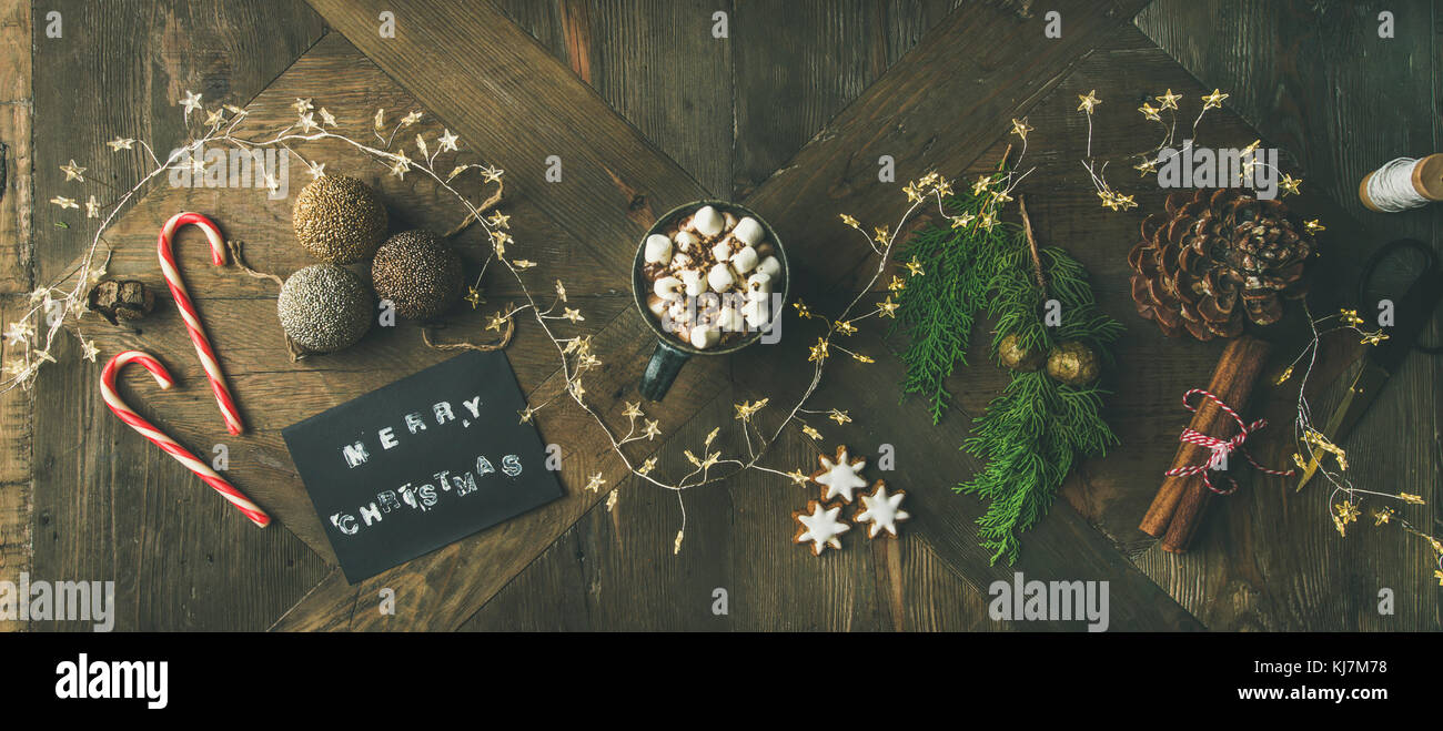 Christmas, New Year holiday background. Flat-lay of greeting card, glittering toys, mug of hot chocolate, cinnamon, - Stock Image