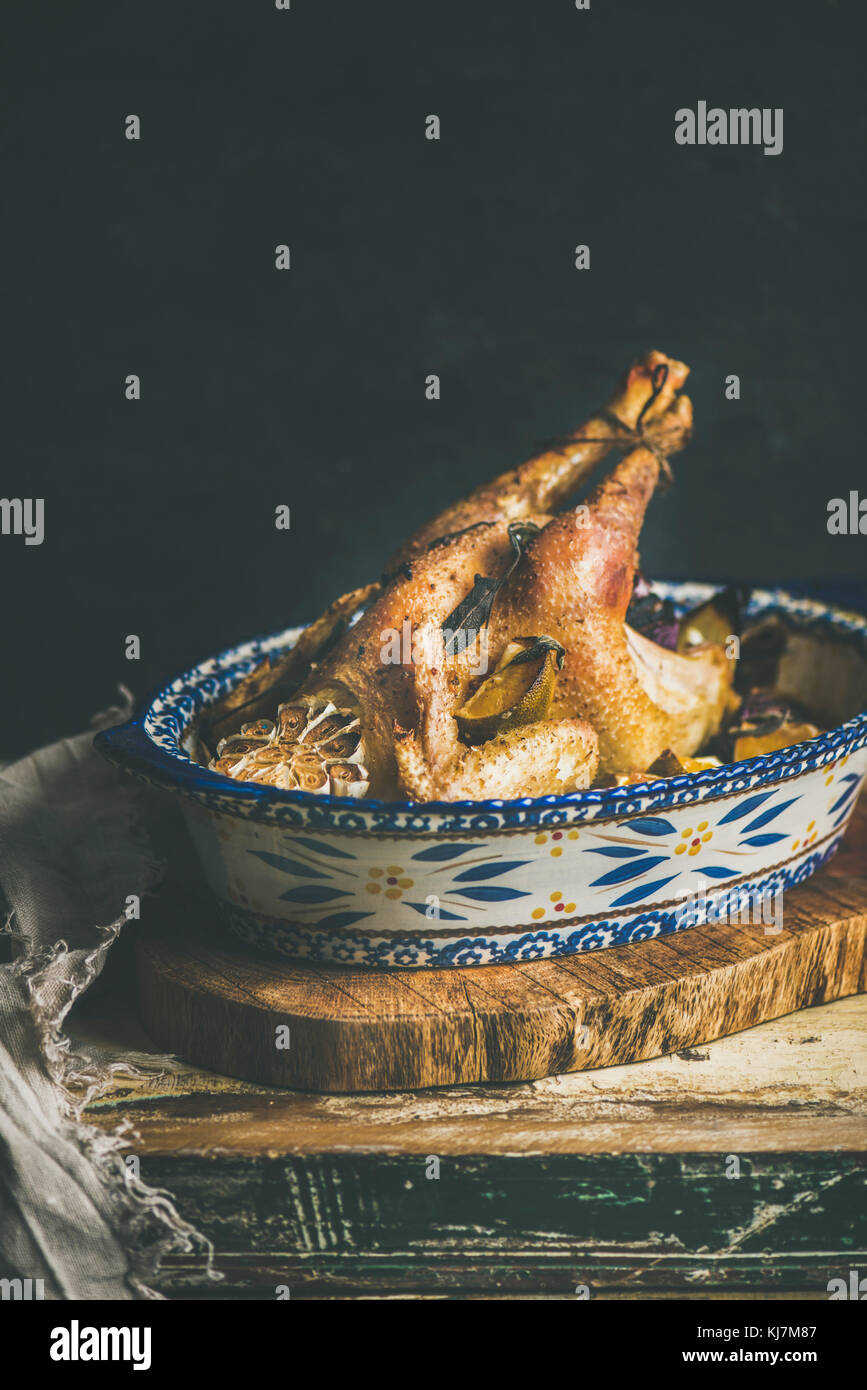Roasted whole chicken for Christmas eve celebration table on rustic wooden board, black wall background, copy space - Stock Image