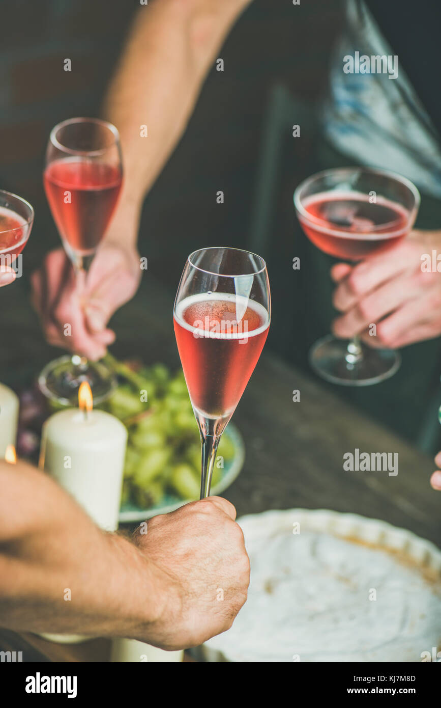 Holiday celebration table setting with food. Friends hands eating and drinking together. People having party, gathering, - Stock Image