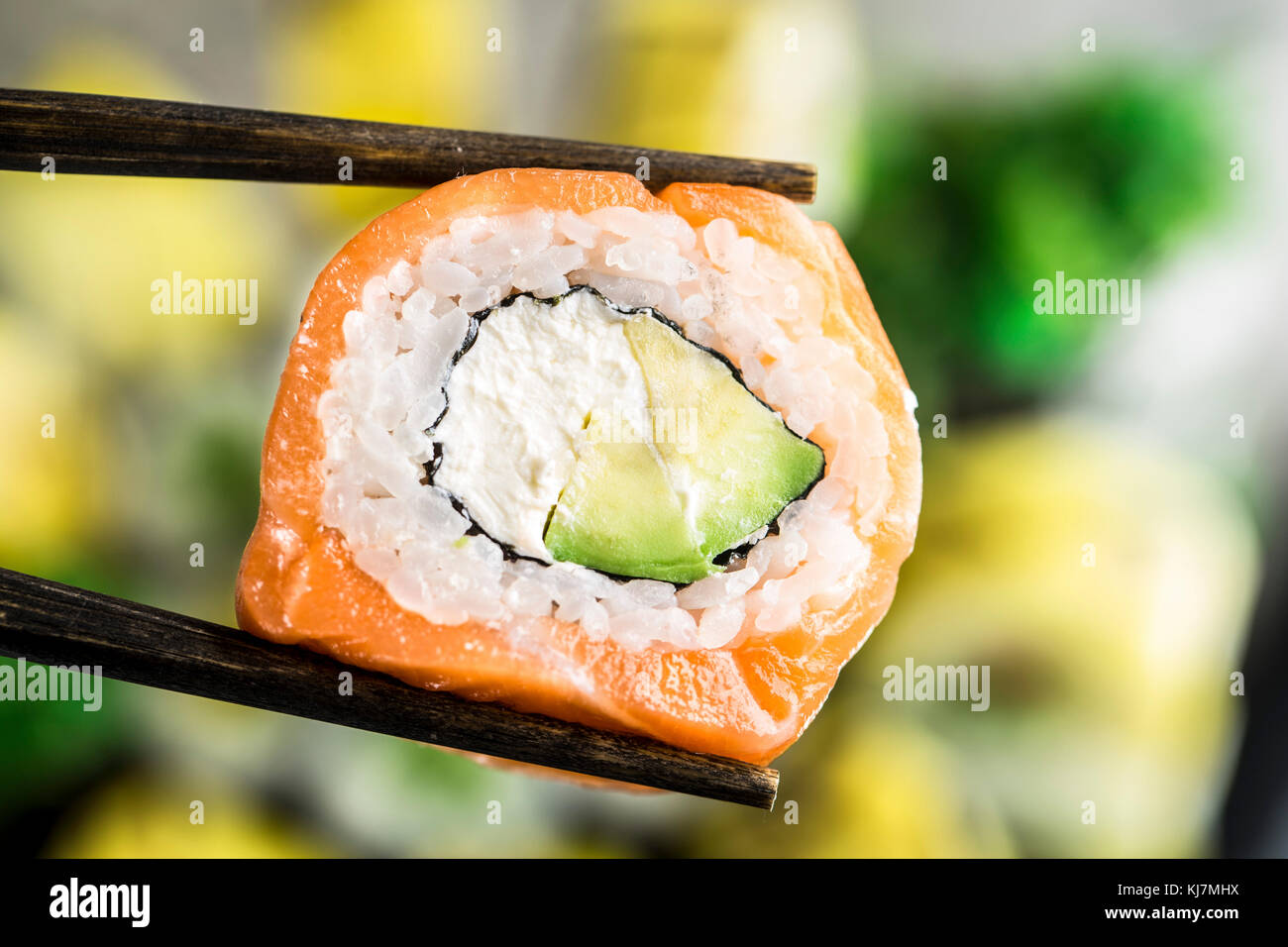Chopsticks hold philadelphia roll over blurred plate of sushi - Stock Image