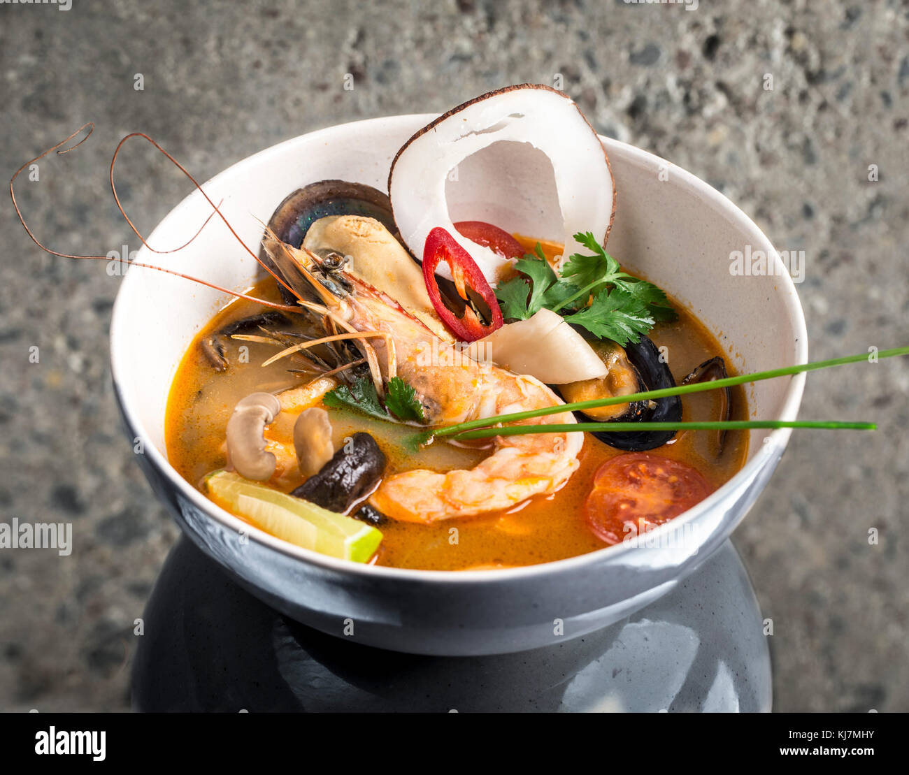 Tom Yum Goong thai soup over concrete background - Stock Image