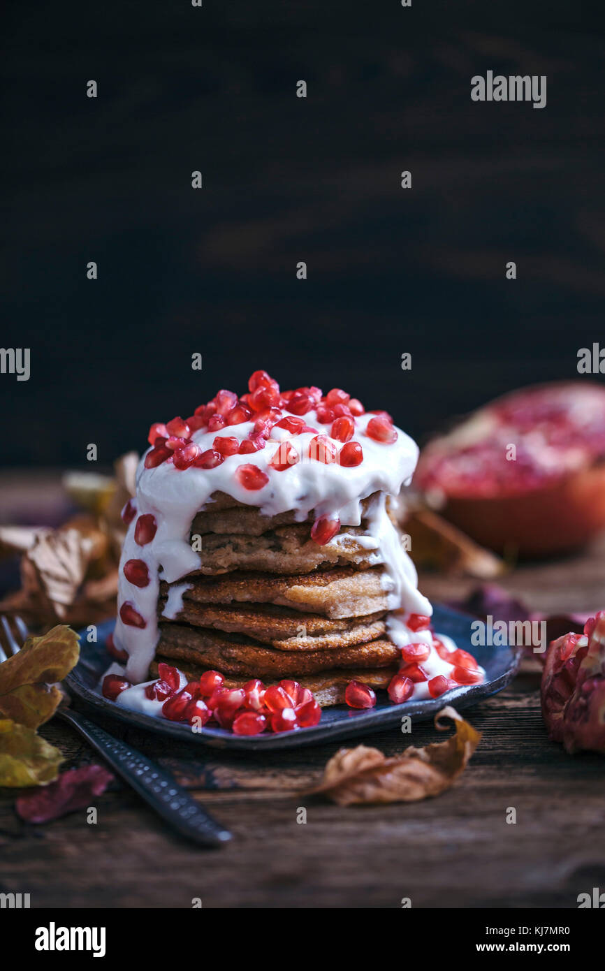 Stack of banana pancakes topped with soya yogurt and pomegranate seeds - Stock Image