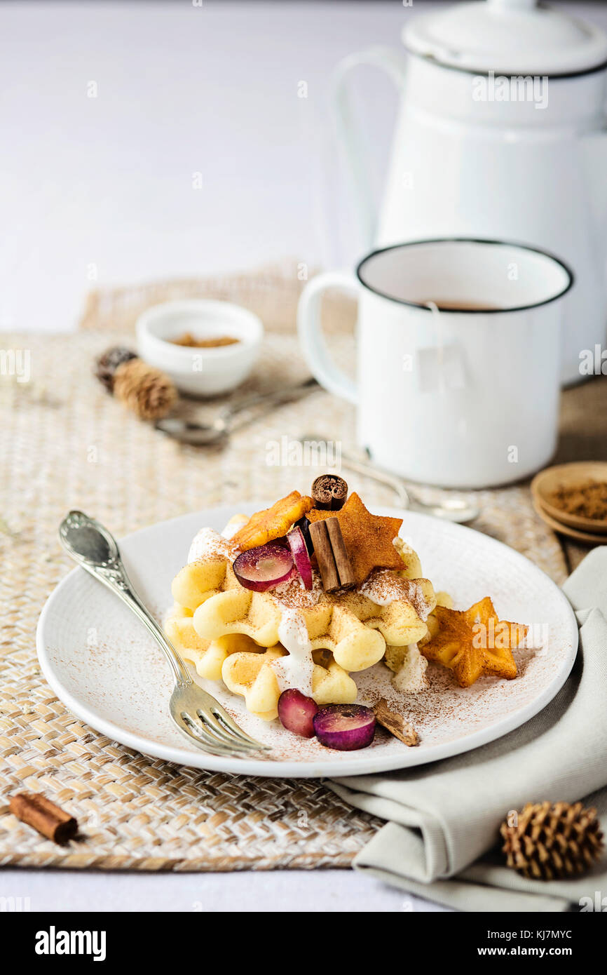 Breakfast table: waffle with fresh fruit, cinnamon and yogurt. Front view. Christmas time - Stock Image