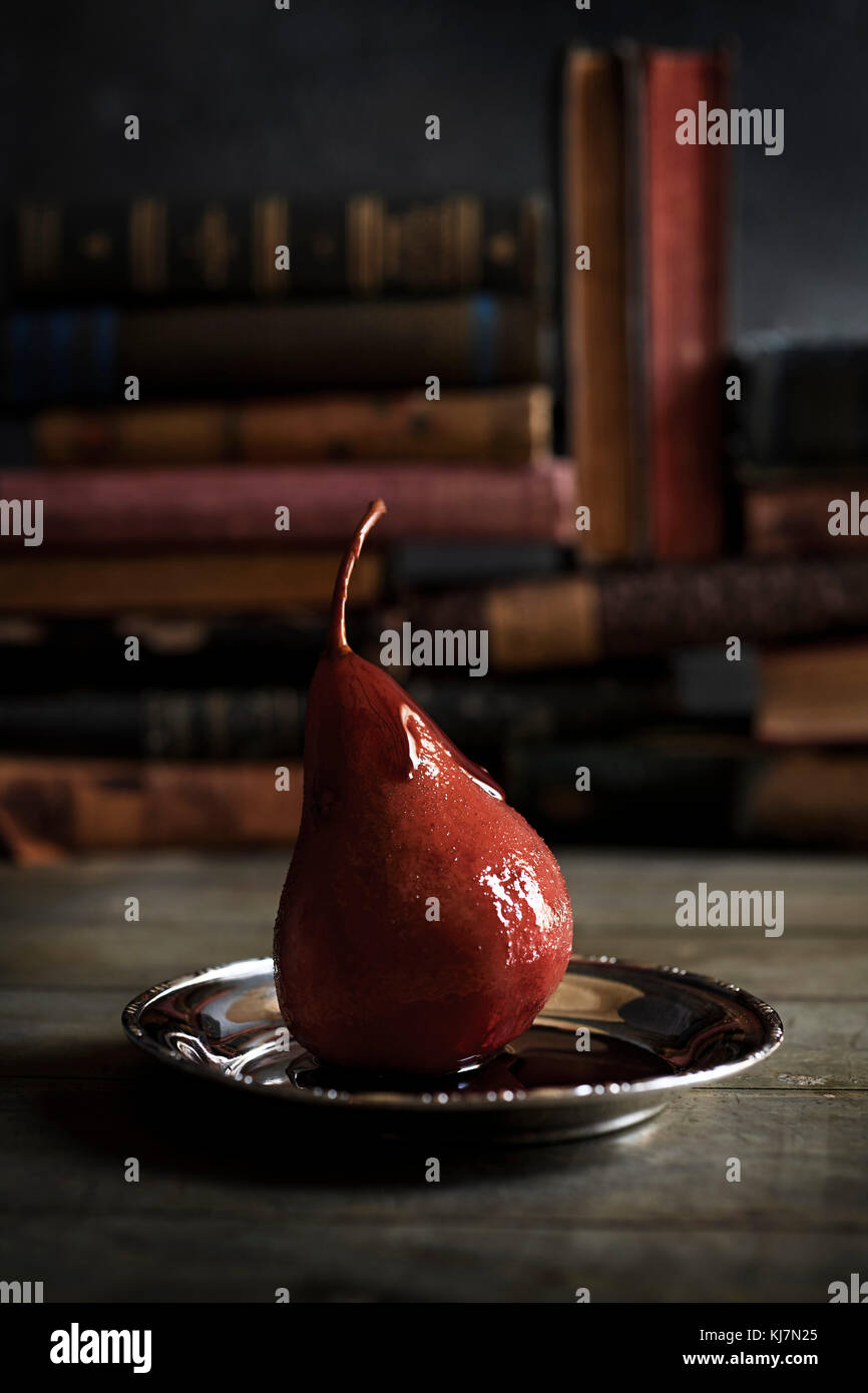 A wine poached pear on silver tray on a table with anitque books in the background. Rustic & moody feel. - Stock Image
