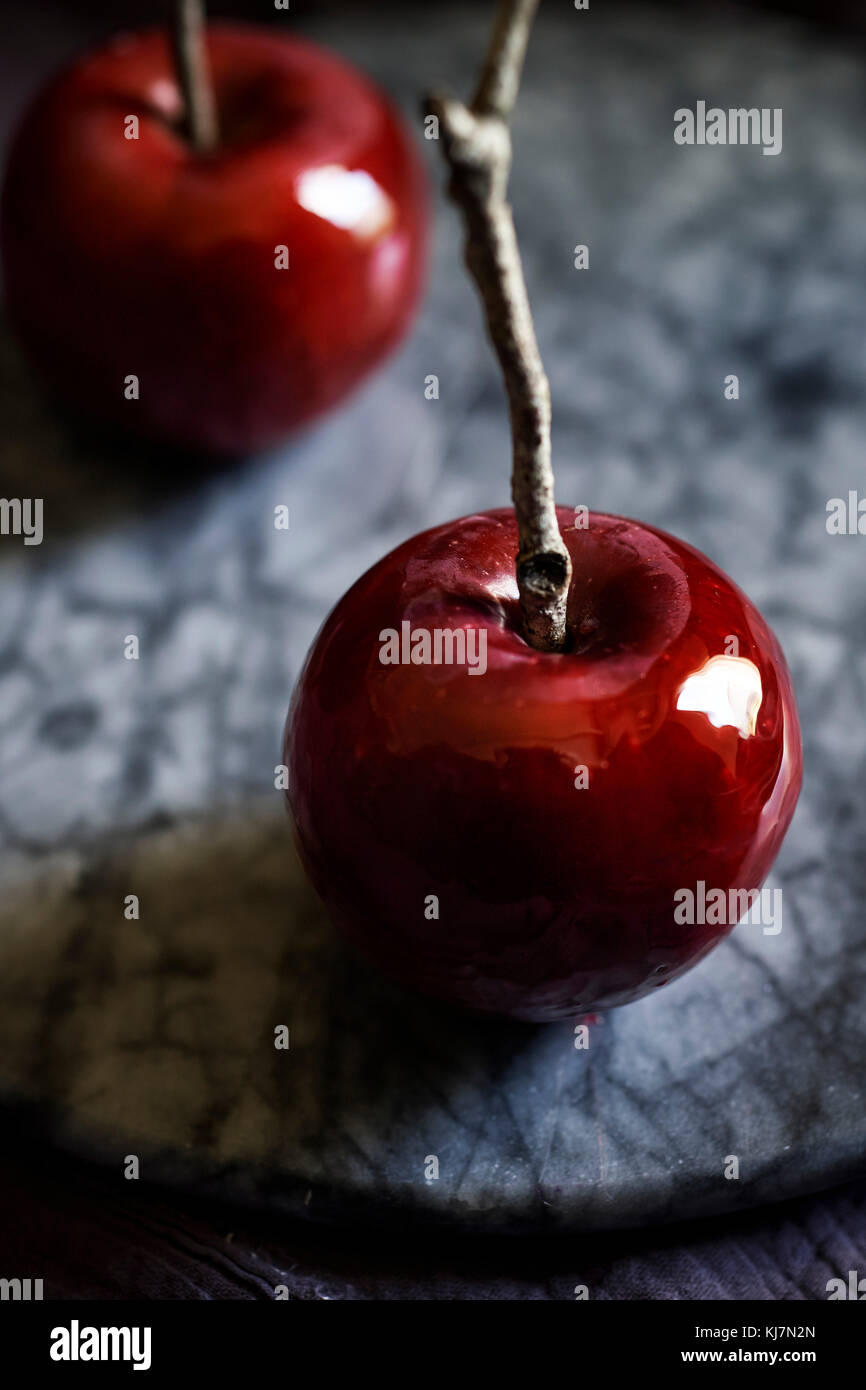 Detail shot of shiny, red, candy apple with twig stick on a marble tray. Moody, dark feel. - Stock Image