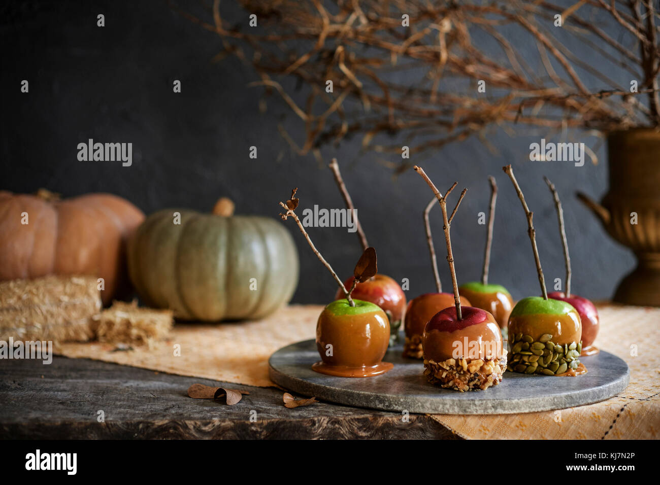 Marble tray of caramel apples with fall decor in the background. Moody and fall themed. - Stock Image