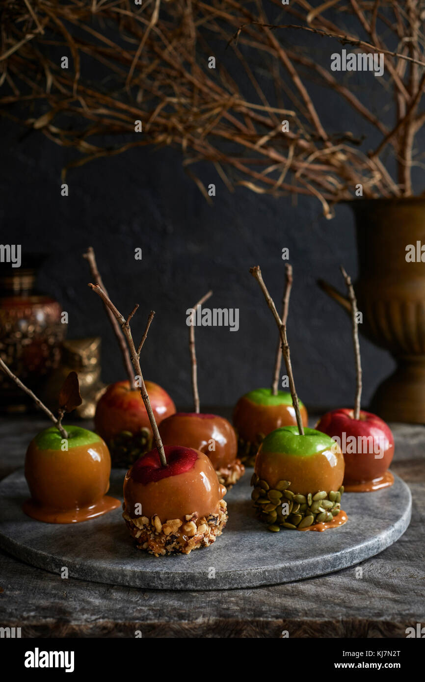 Marble tray full of caramel apples with stick handles covered in nuts and seeds. Moody fall foliage in the background. Stock Photo