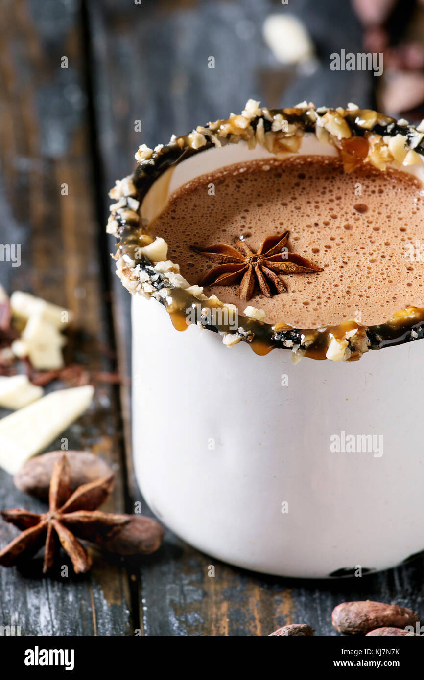 Vintage mug of hot chocolate, decor with nuts, caramel, spices. Ingredients above. Chopped dark and white chocolate, Stock Photo