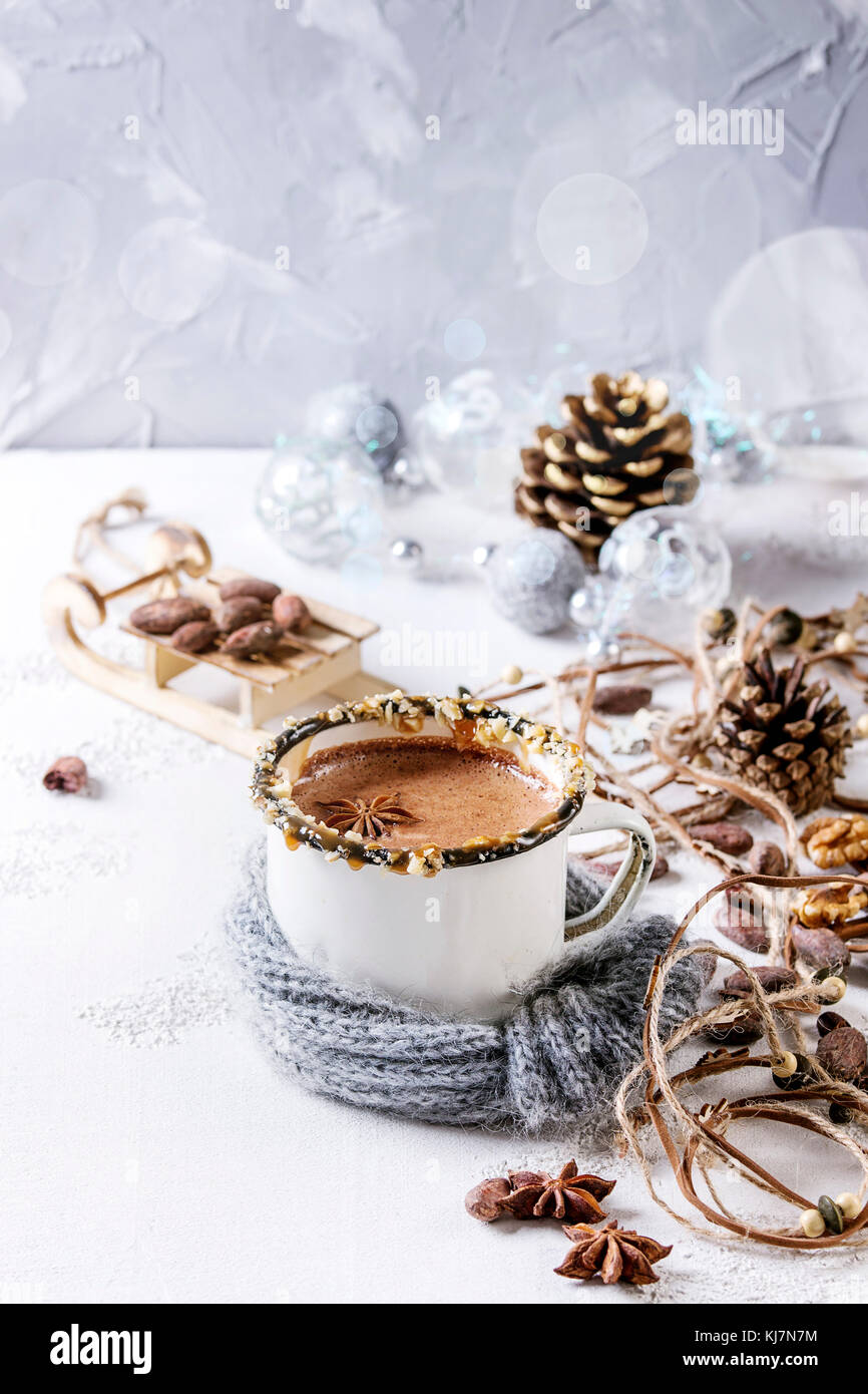 Vintage mug in wool scarf of hot chocolate, decor with nuts, caramel, spices. Ingredients and Christmas toys above Stock Photo