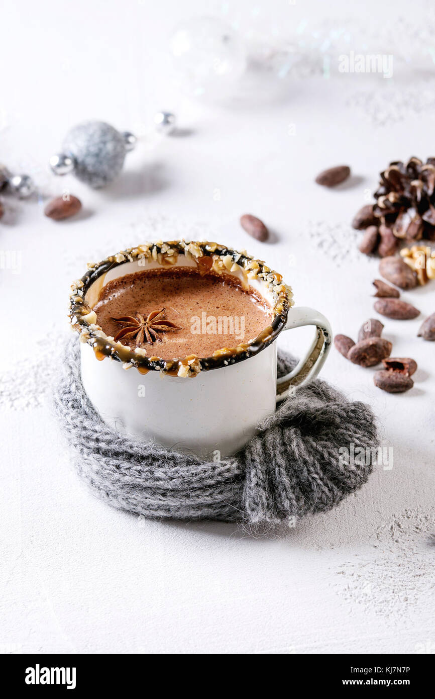 Vintage mug in wool scarf of hot chocolate, decor with nuts, caramel, spices. Ingredients and Christmas toys above - Stock Image