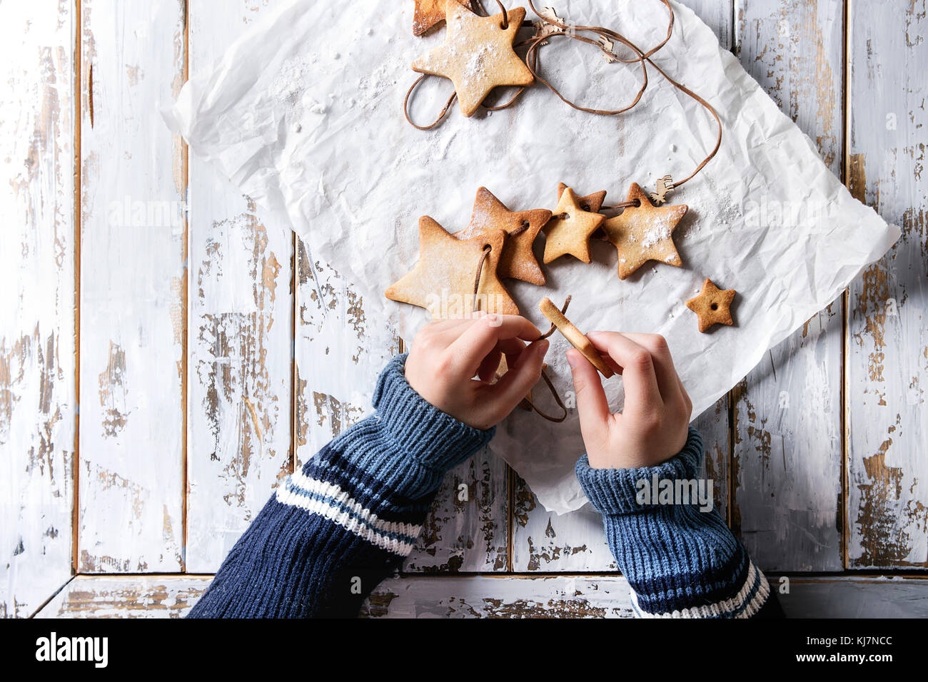 Child hands make garland of homemade shortbread star shape sugar cookies different size on thread on baking paper - Stock Image