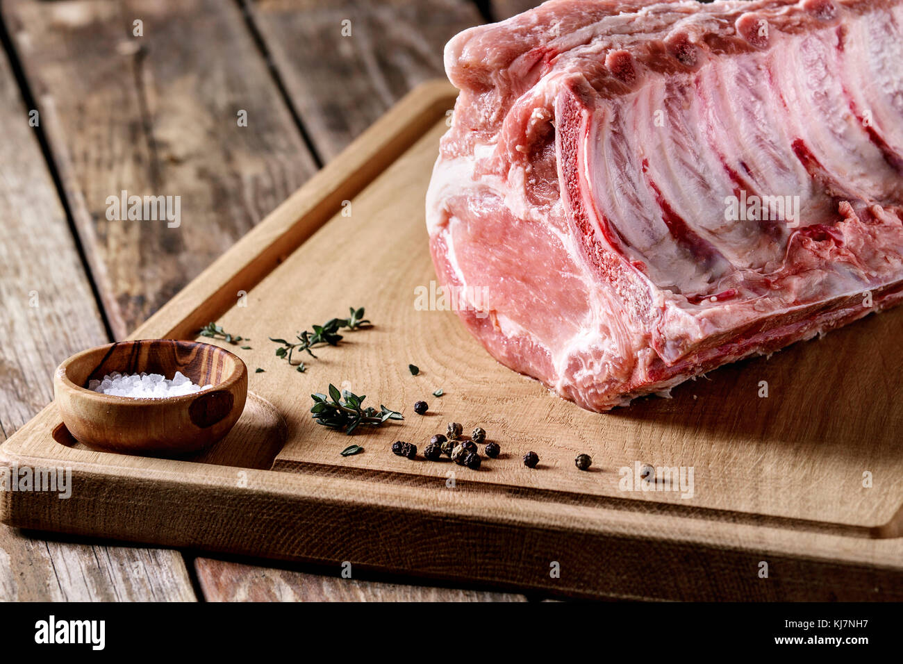 Fresh raw uncooked whole rack of pork loin with ribs on wooden cutting board with salt, thyme and butcher clever - Stock Image