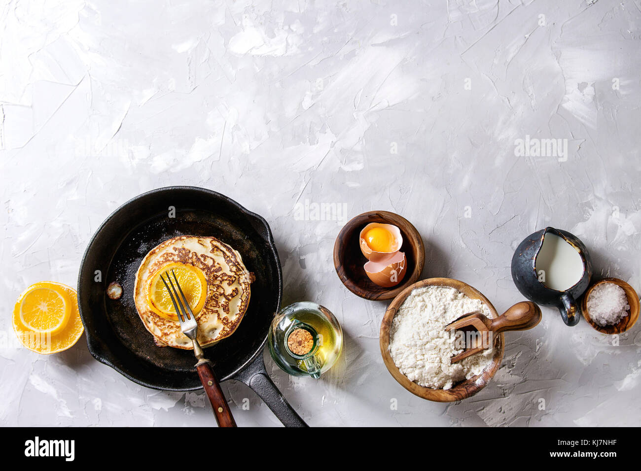 Homemade pancakes with fried orange in cast-iron pan and ingredients above. Wooden bowls of flour, yolk, salt, milk, Stock Photo