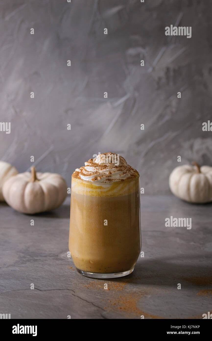 Glass of spicy pumpkin latte with whipped cream and cinnamon standing on gray kitchen table with decorative white - Stock Image